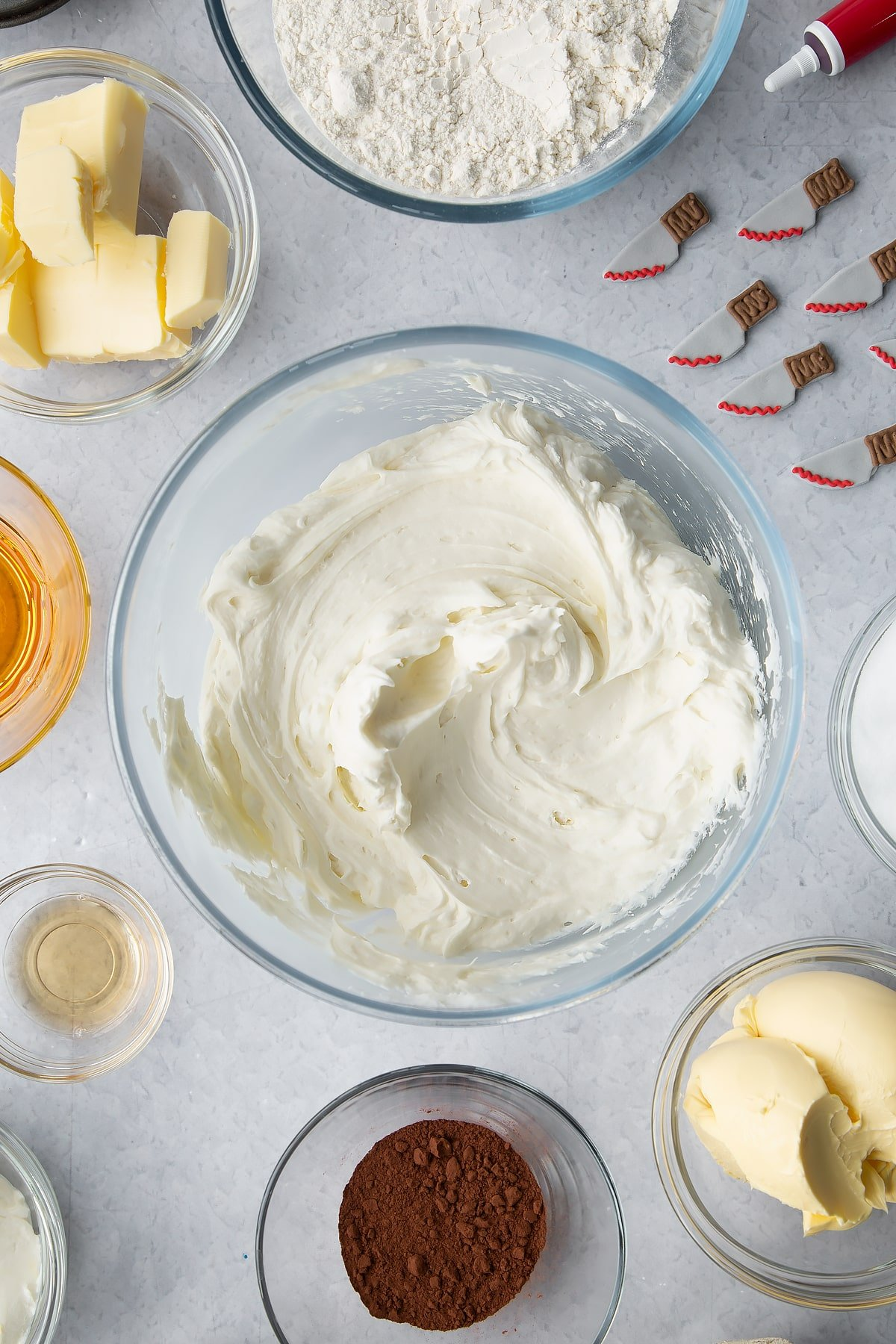 Cream cheese frosting in a glass bowl. Ingredients to make red velvet Halloween cupcakes surround the bowl.