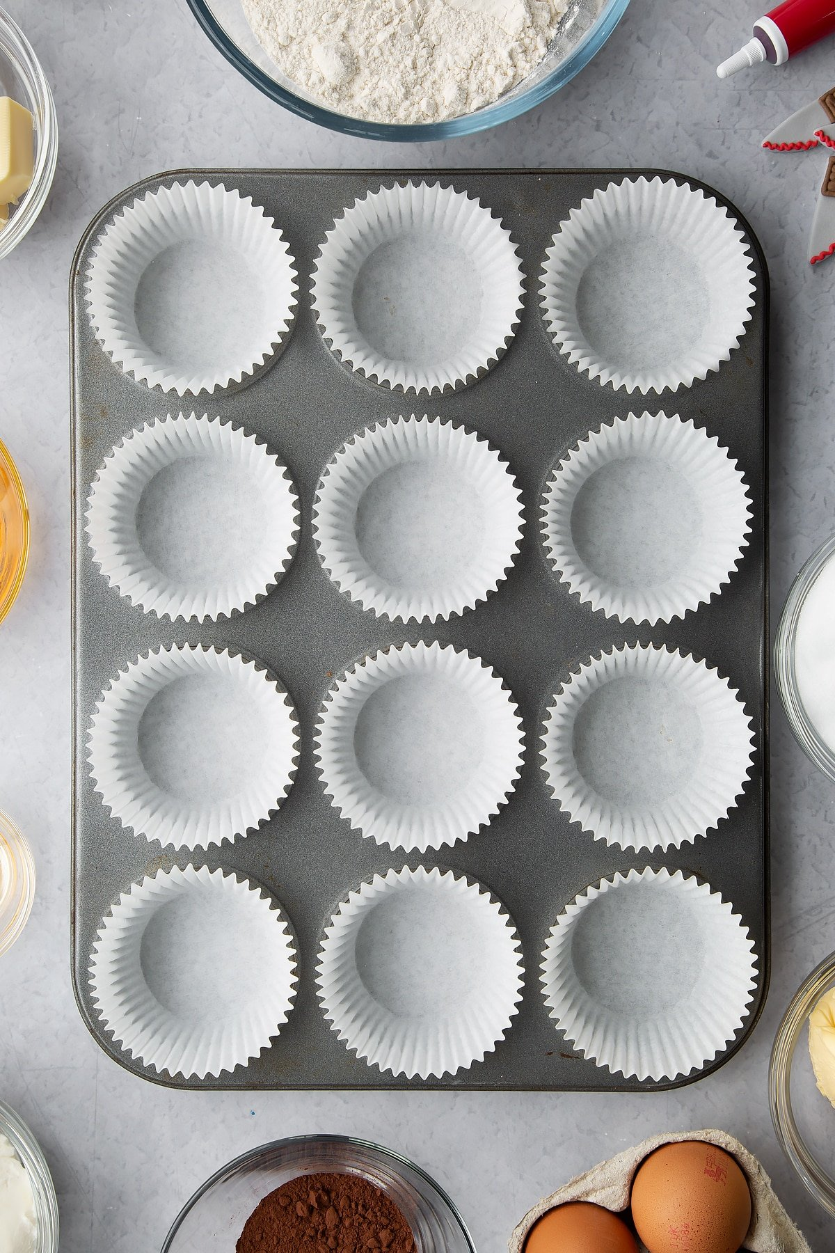 A muffin tray lined with cupcake cases. Ingredients to make red velvet Halloween cupcakes surround the tin.