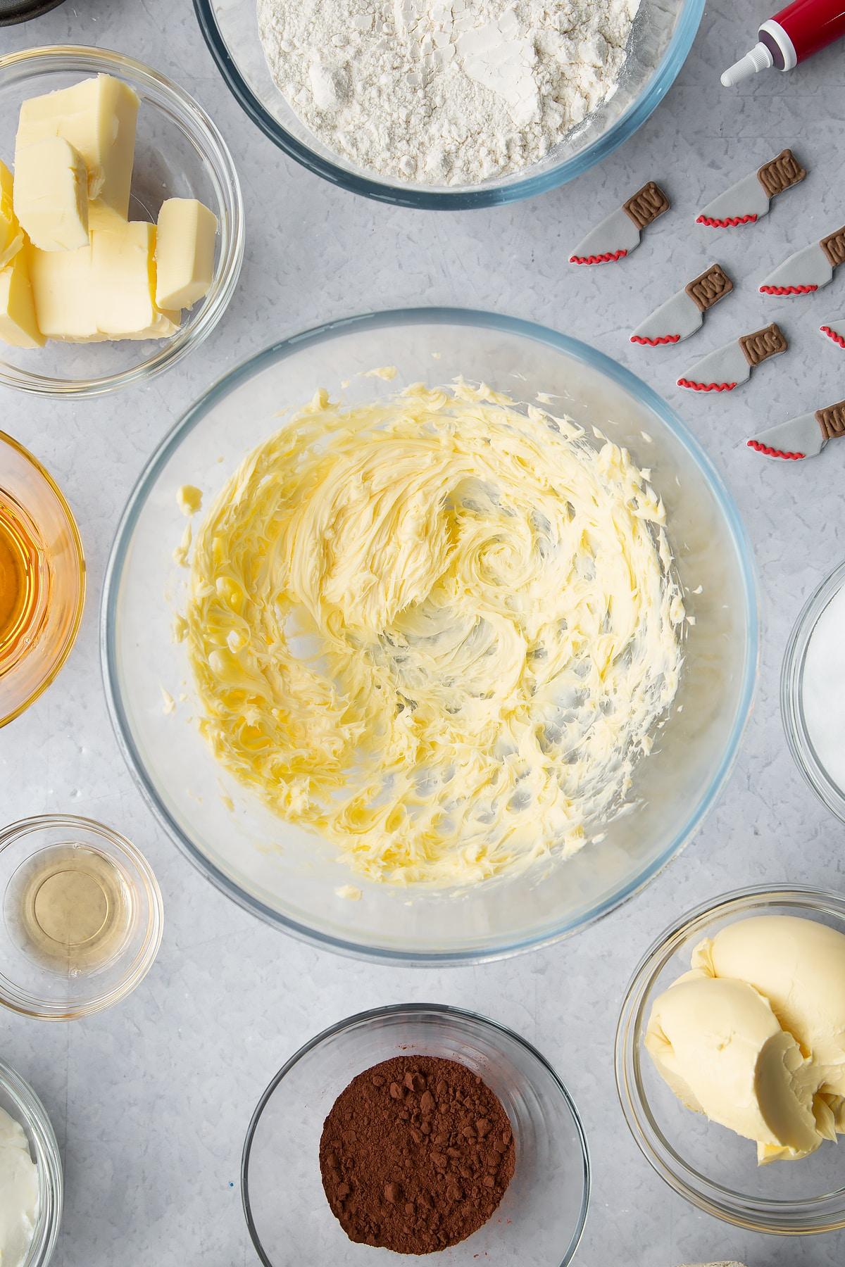Whipped butter in a glass bowl. Ingredients to make red velvet Halloween cupcakes surround the bowl.