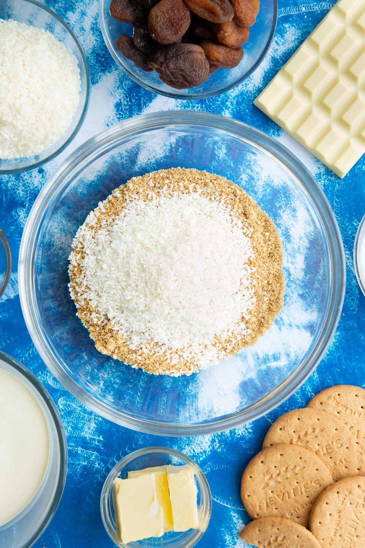 Crushed biscuits and desiccated coconut in a bowl. Ingredients to make an apricot cheesecake surround the bowl.