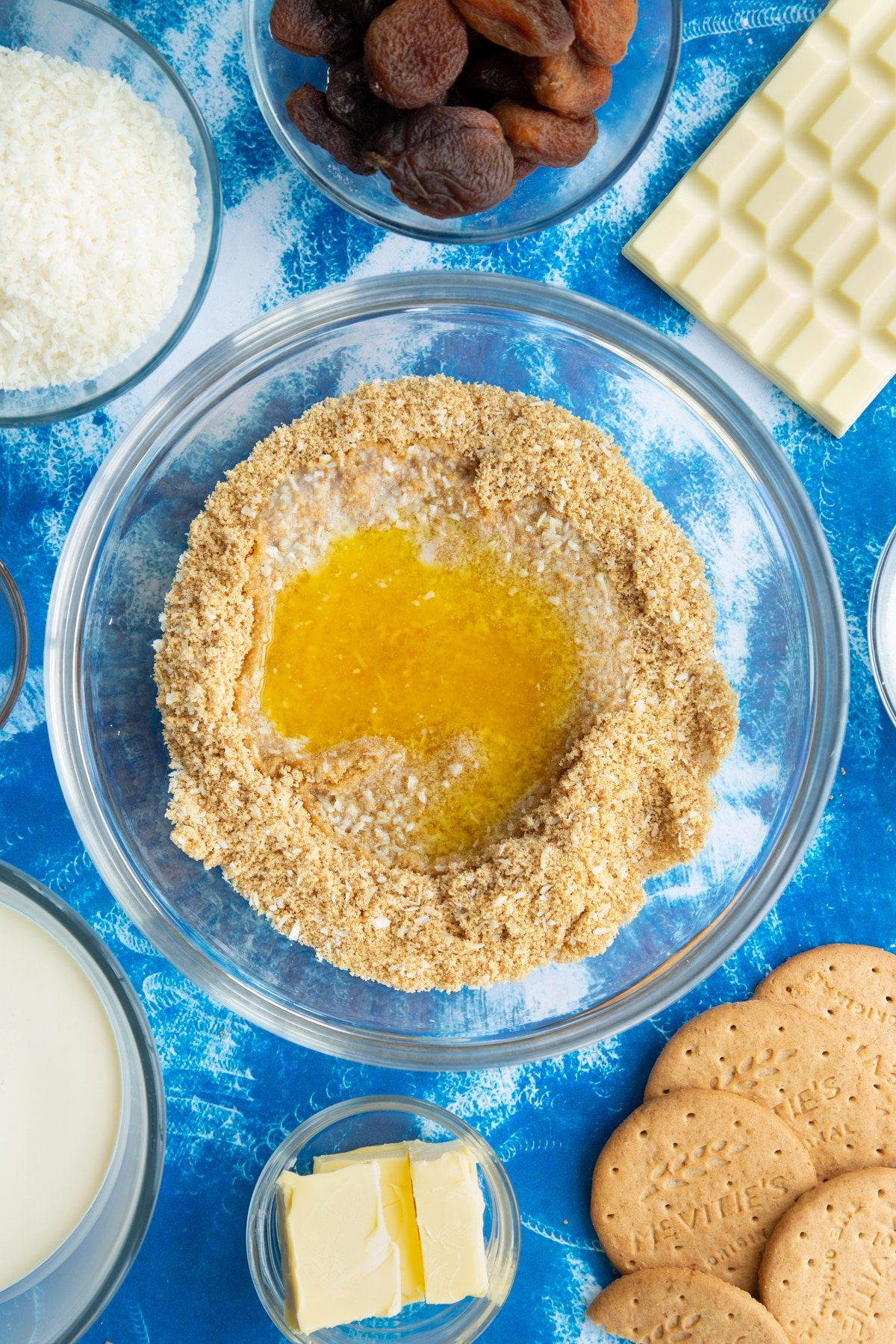 Crushed biscuits and desiccated coconut mixed together with melted butter on top in a bowl. Ingredients to make an apricot cheesecake surround the bowl.