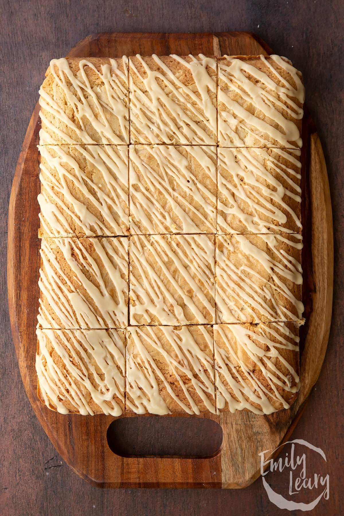 Freshly baked Baileys blondie drizzled with Baileys icing, cut into 12 pieces on a wooden board.