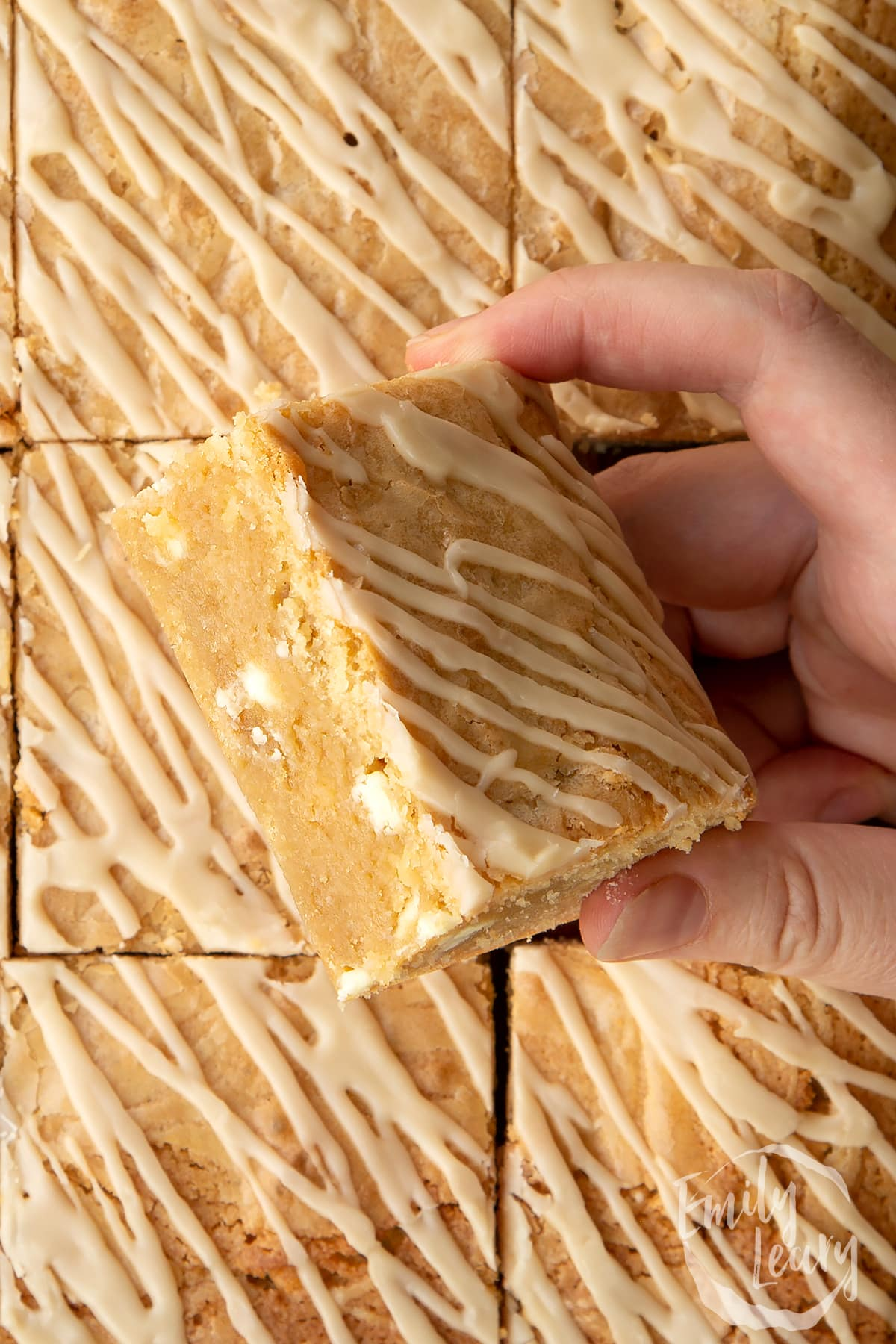 Hand holding a square of Baileys blondie above more blondies.