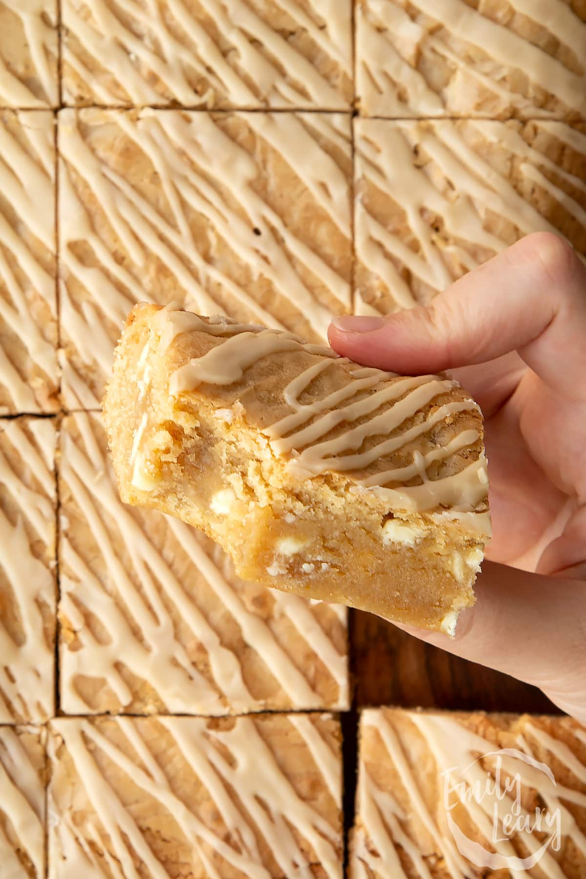 Hand holding a square of Baileys blondie with a bite out of it above more blondies.