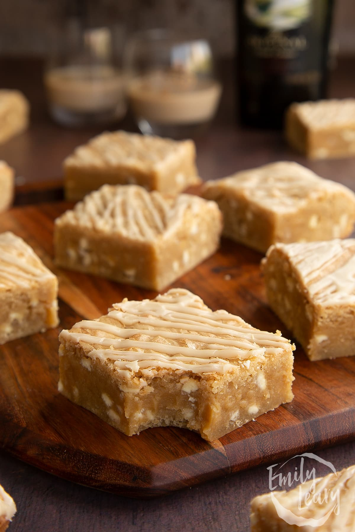 Baileys blondies on a wooden board. One has a bite out of it.