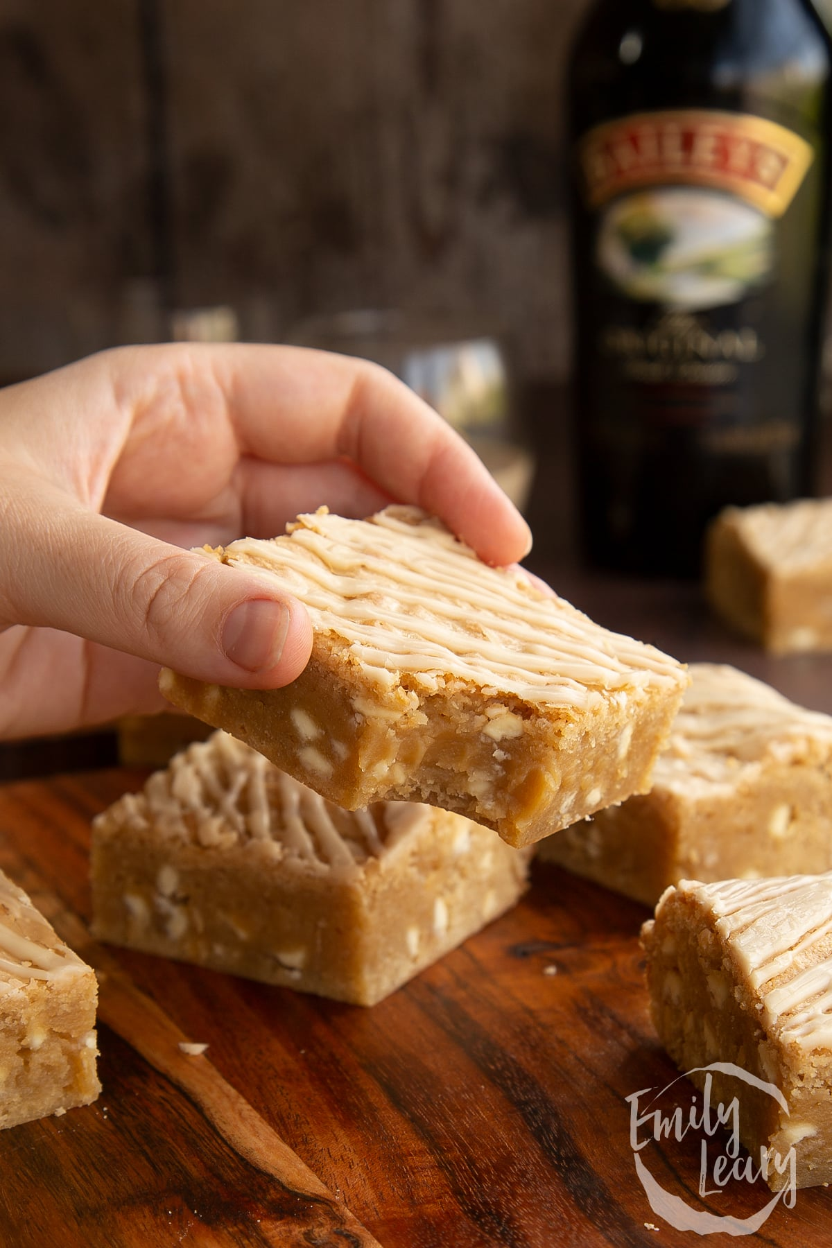 Baileys blondies on a wooden board. A hand holds one with a bite out of it.