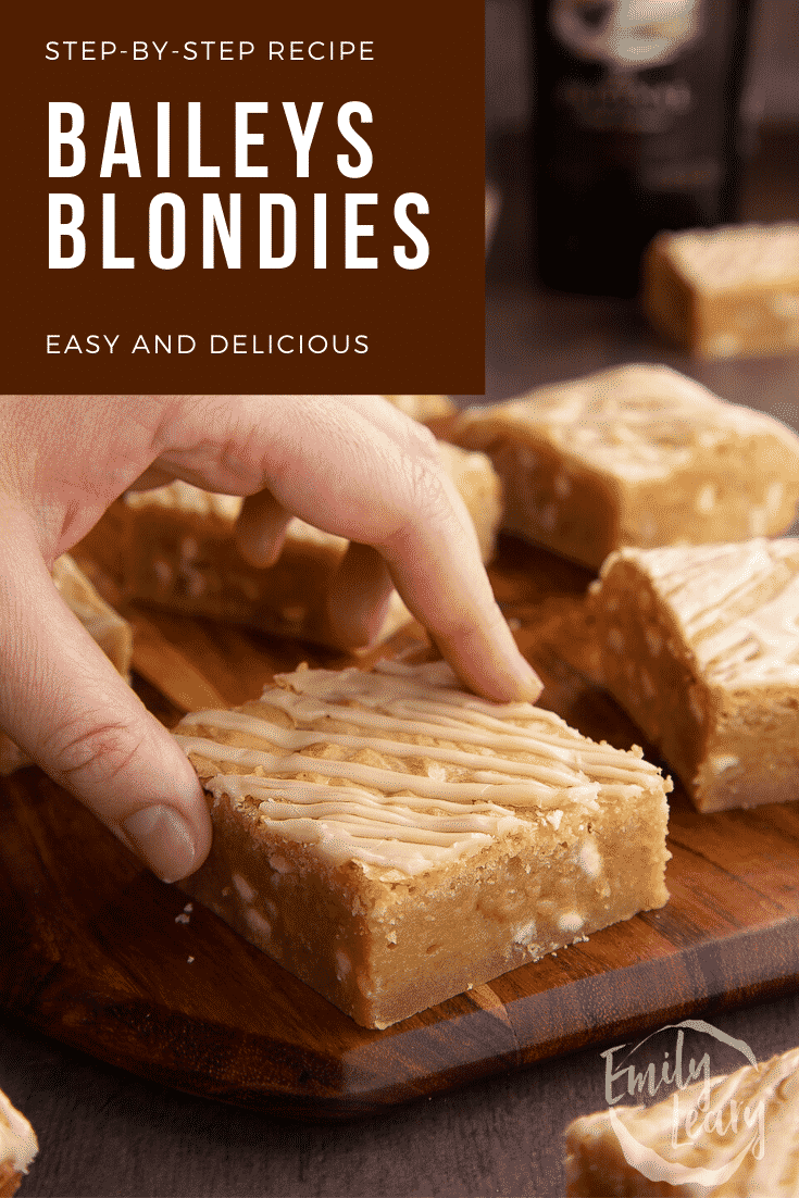 Baileys blondie on a wooden board. A hand reaches for it. Caption reads: Step-by-step recipe. Baileys blondies. Easy and delicious.