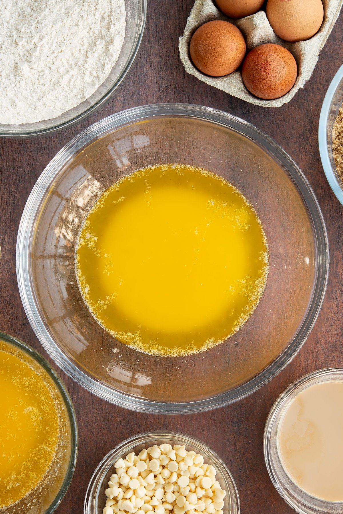 Melted butter in a glass mixing bowl. Ingredients to make Baileys blondies surround the bowl.