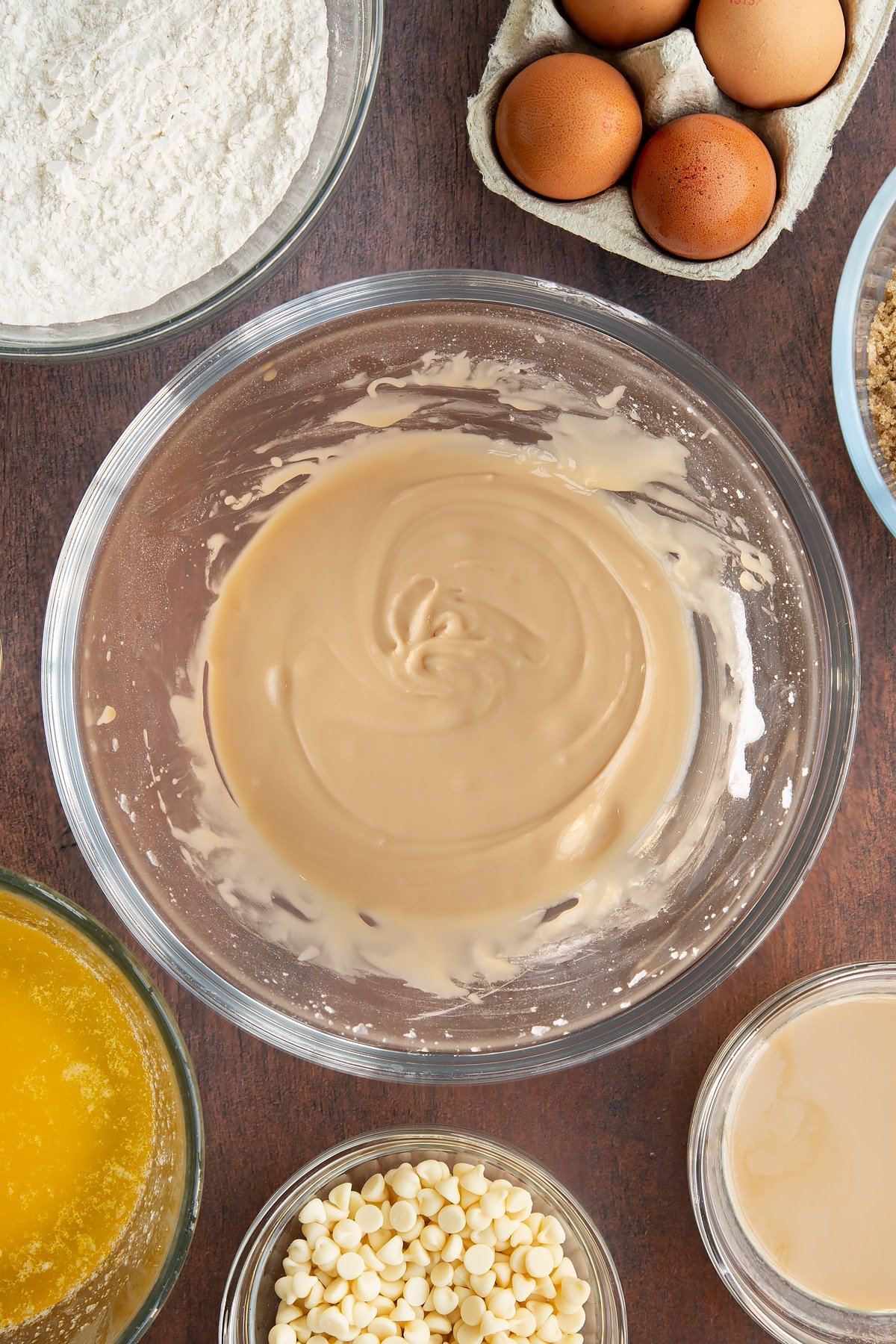 Baileys icing in a glass mixing bowl. Ingredients to make Baileys blondies surround the bowl.