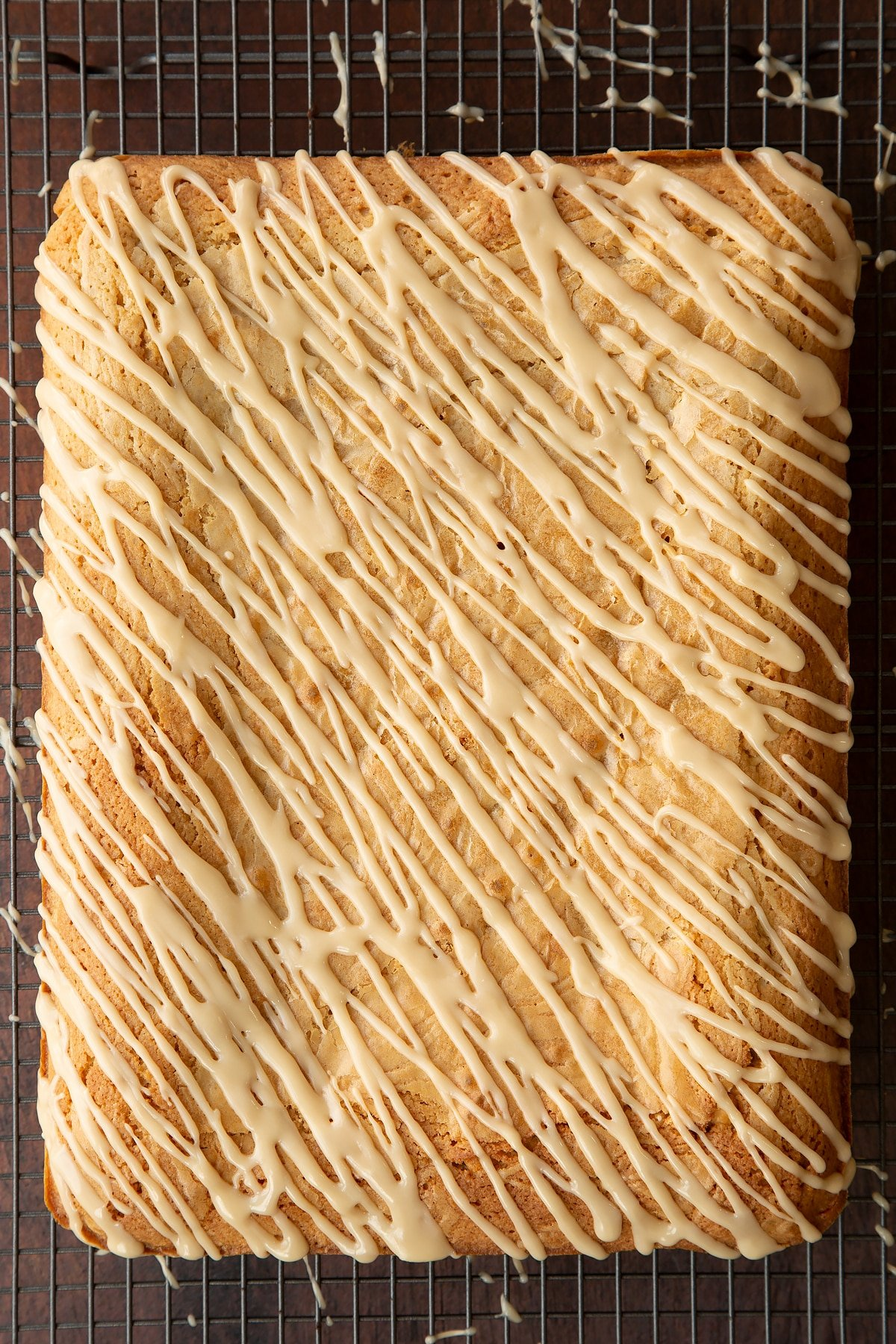 Freshly baked Baileys blondie drizzled with Baileys icing on a wire rack.
