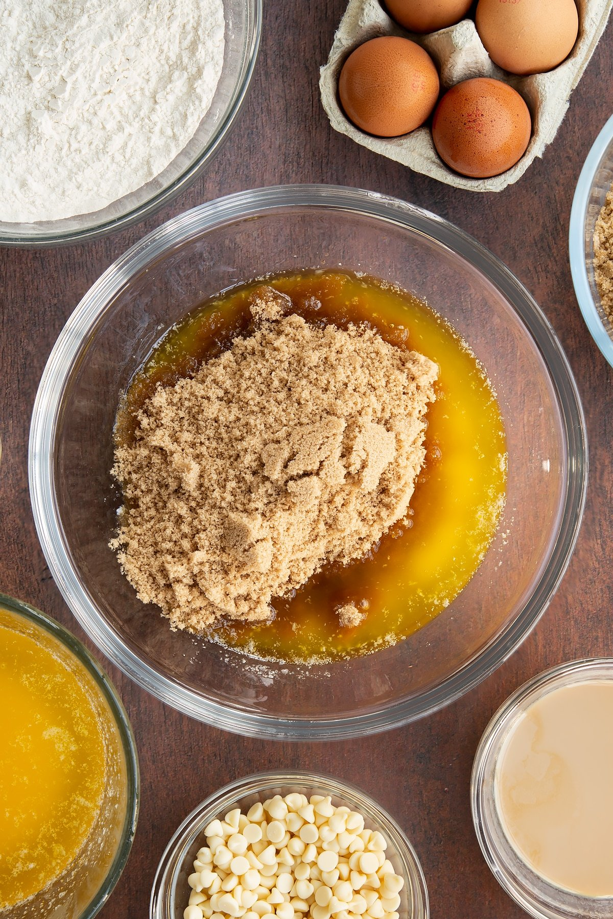 Melted butter and soft brown sugar in a glass mixing bowl. Ingredients to make Baileys blondies surround the bowl.
