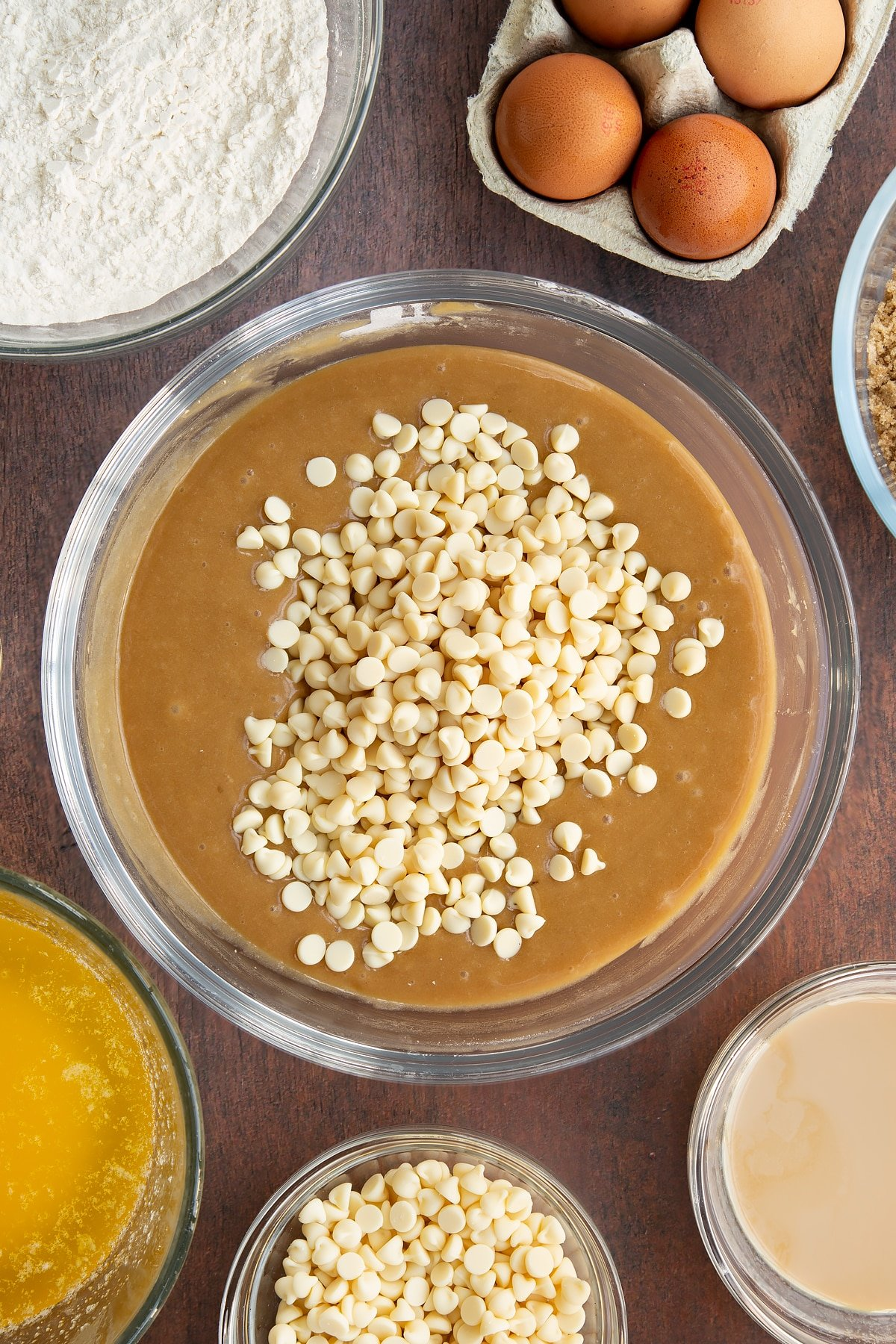 Baileys blondie batter in a glass mixing bowl with white chocolate chips on top. Ingredients to make Baileys blondies surround the bowl.