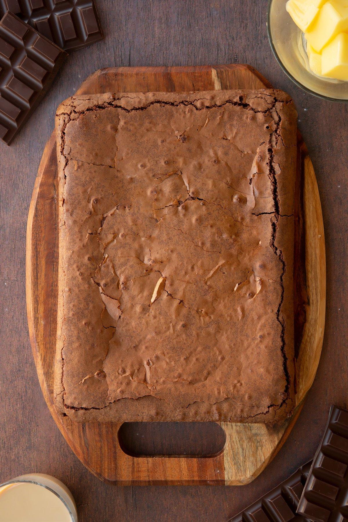 Freshly baked Baileys brownie on a board.