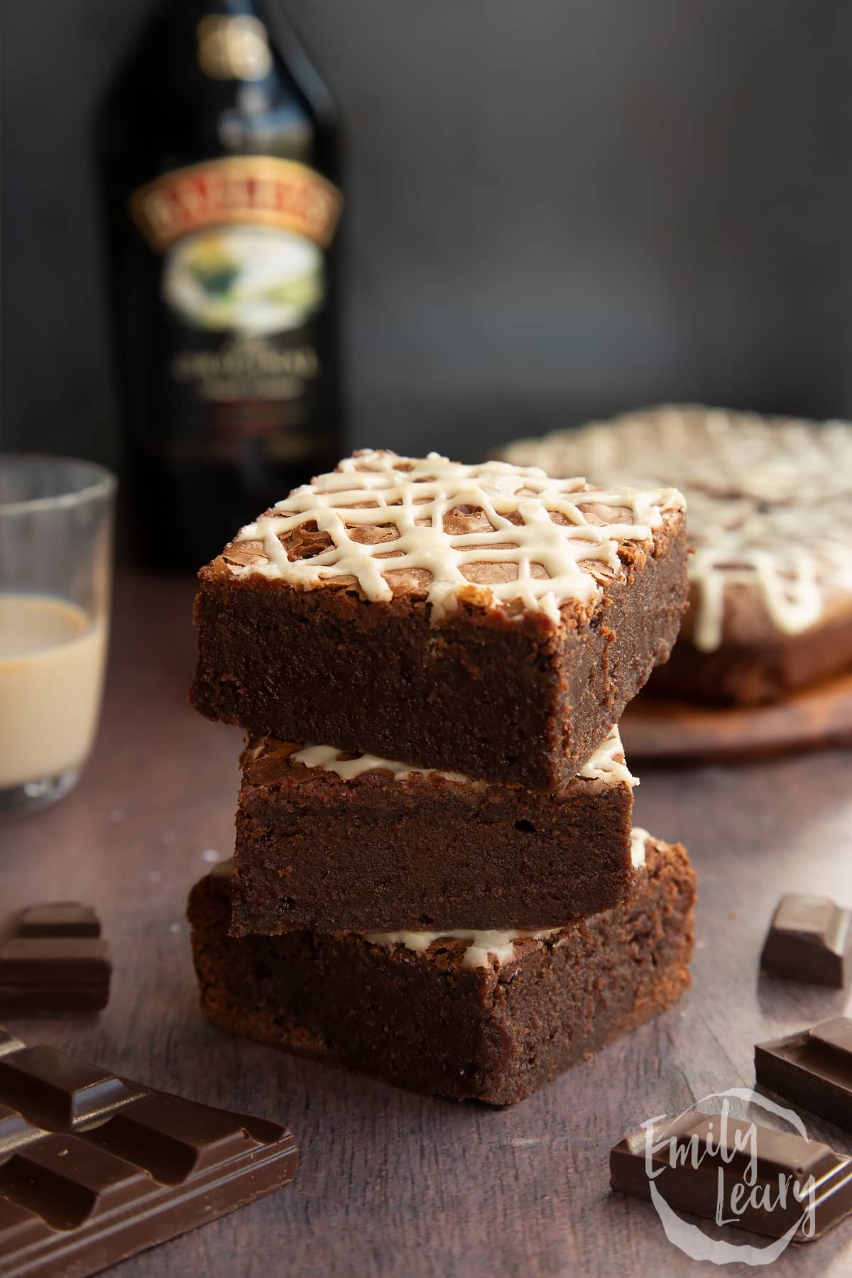 Stack of iced Baileys brownies, with more brownies and a bottle of Baileys in the background.