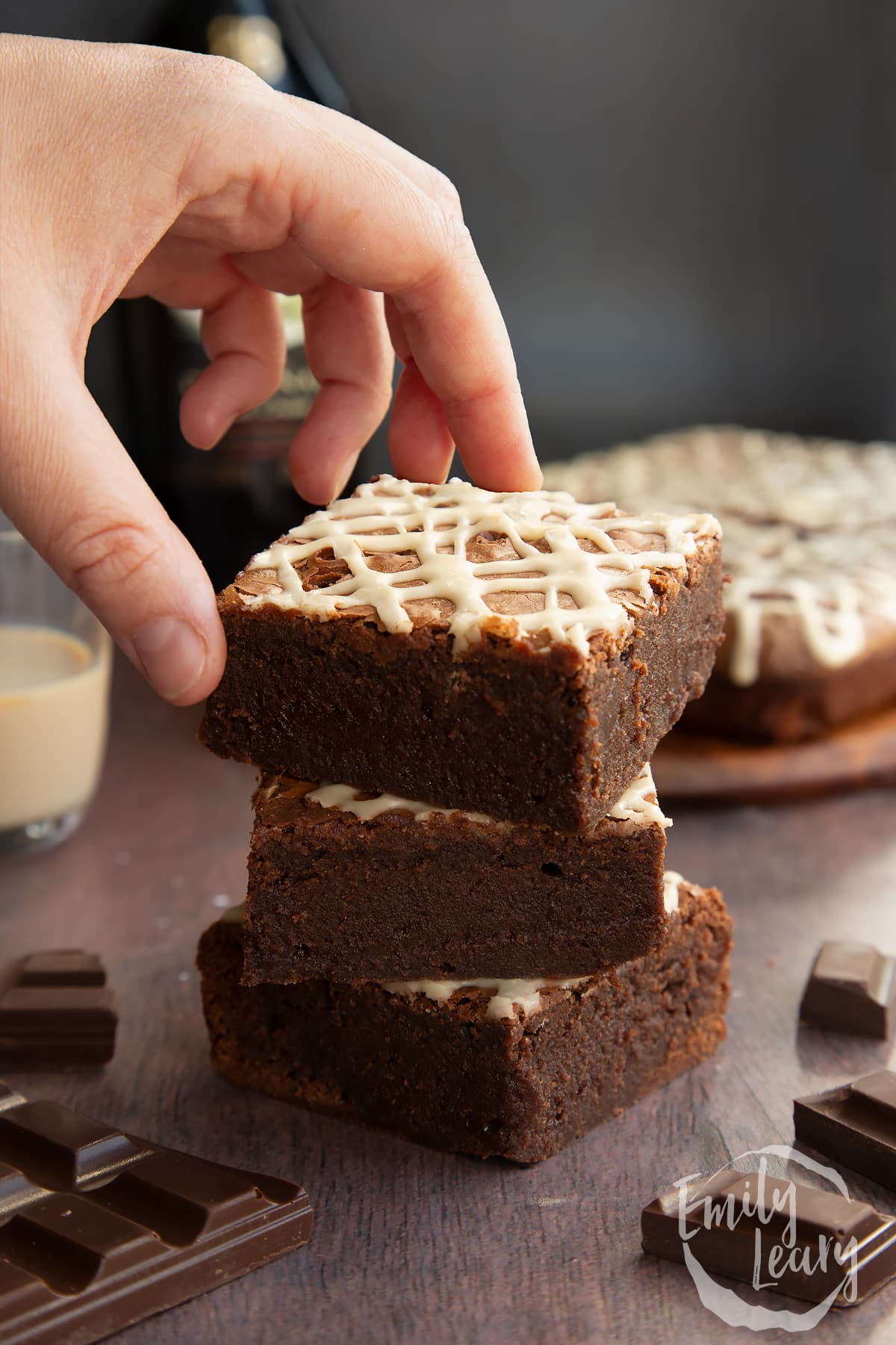 Stack of iced Baileys brownies, with more brownies and a bottle of Baileys in the background. A hand reaches for one.
