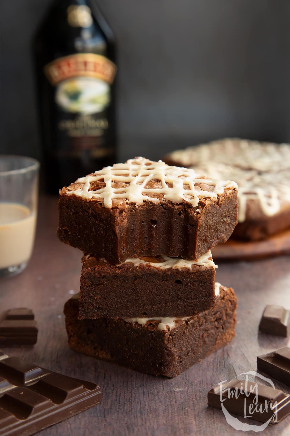 Stack of iced Baileys brownies, with more brownies and a bottle of Baileys in the background. One brownie has a bite out of it.