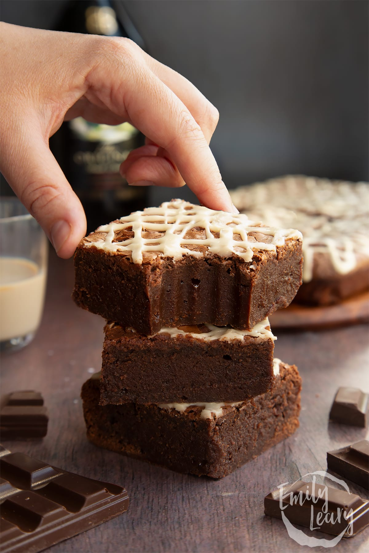 Stack of iced Baileys brownies, with more brownies and a bottle of Baileys in the background. One has a bite out if and a hand reaches for it.