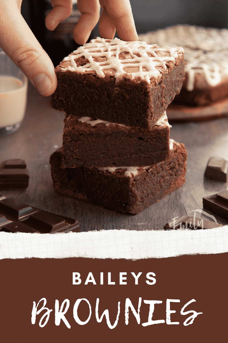 Stack of iced Baileys brownies, with more brownies and a bottle of Baileys in the background. A hand reaches for one. Caption reads: Baileys brownies.