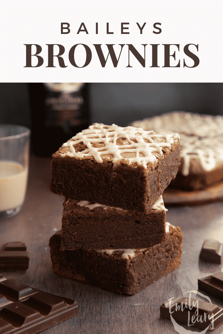 A stack of iced Baileys brownies, with more brownies and a bottle of Baileys in the background. Caption reads: Baileys brownies.