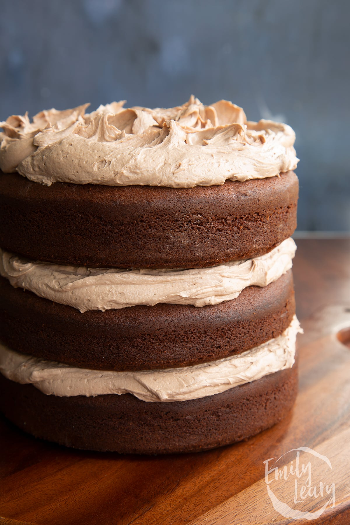 Close up of three tier chocolate Baileys cake, sandwiched and topped with Baileys buttercream frosting.