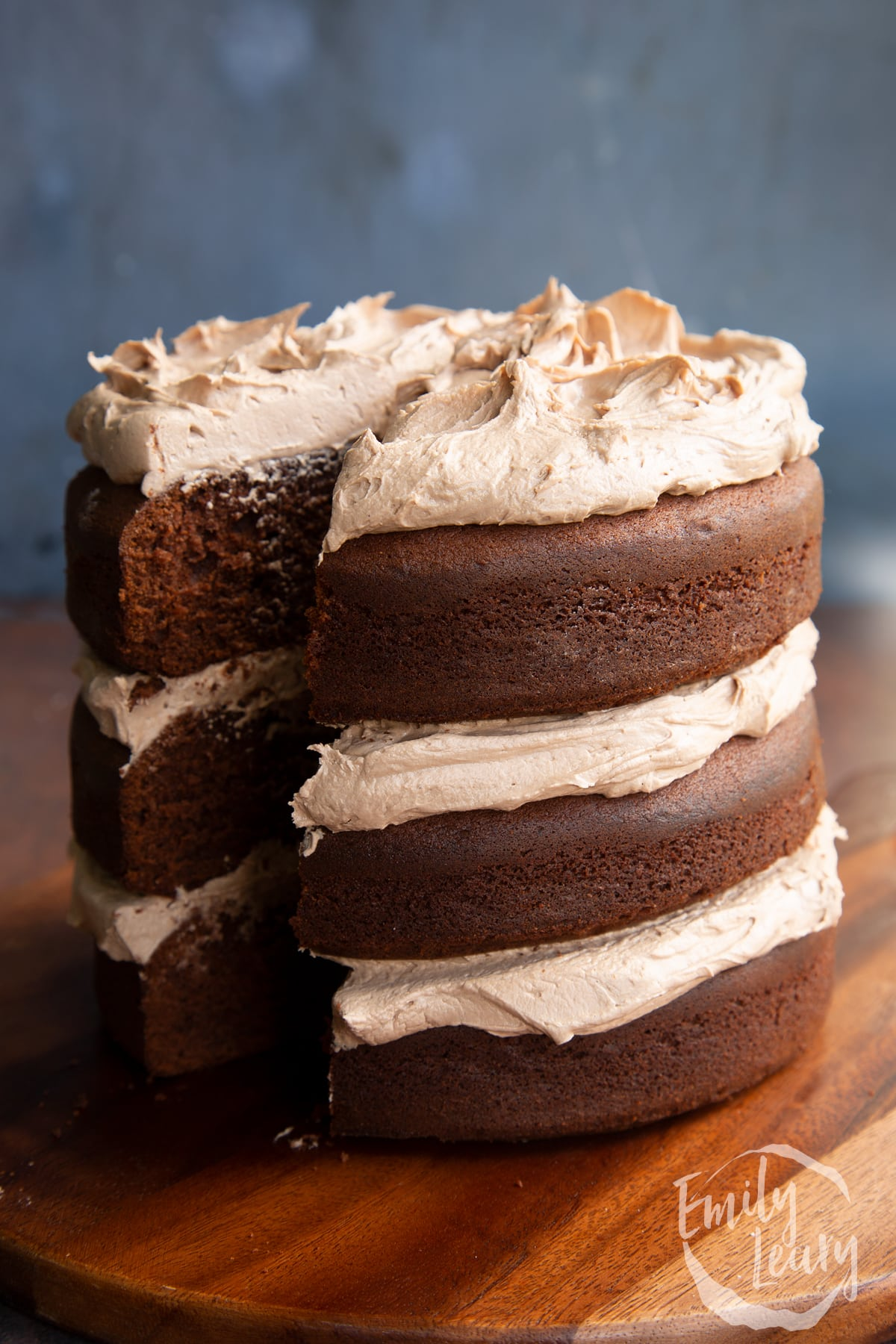 Three tier chocolate Baileys cake, sandwiched and topped with Baileys buttercream frosting. A slice has been cut away.