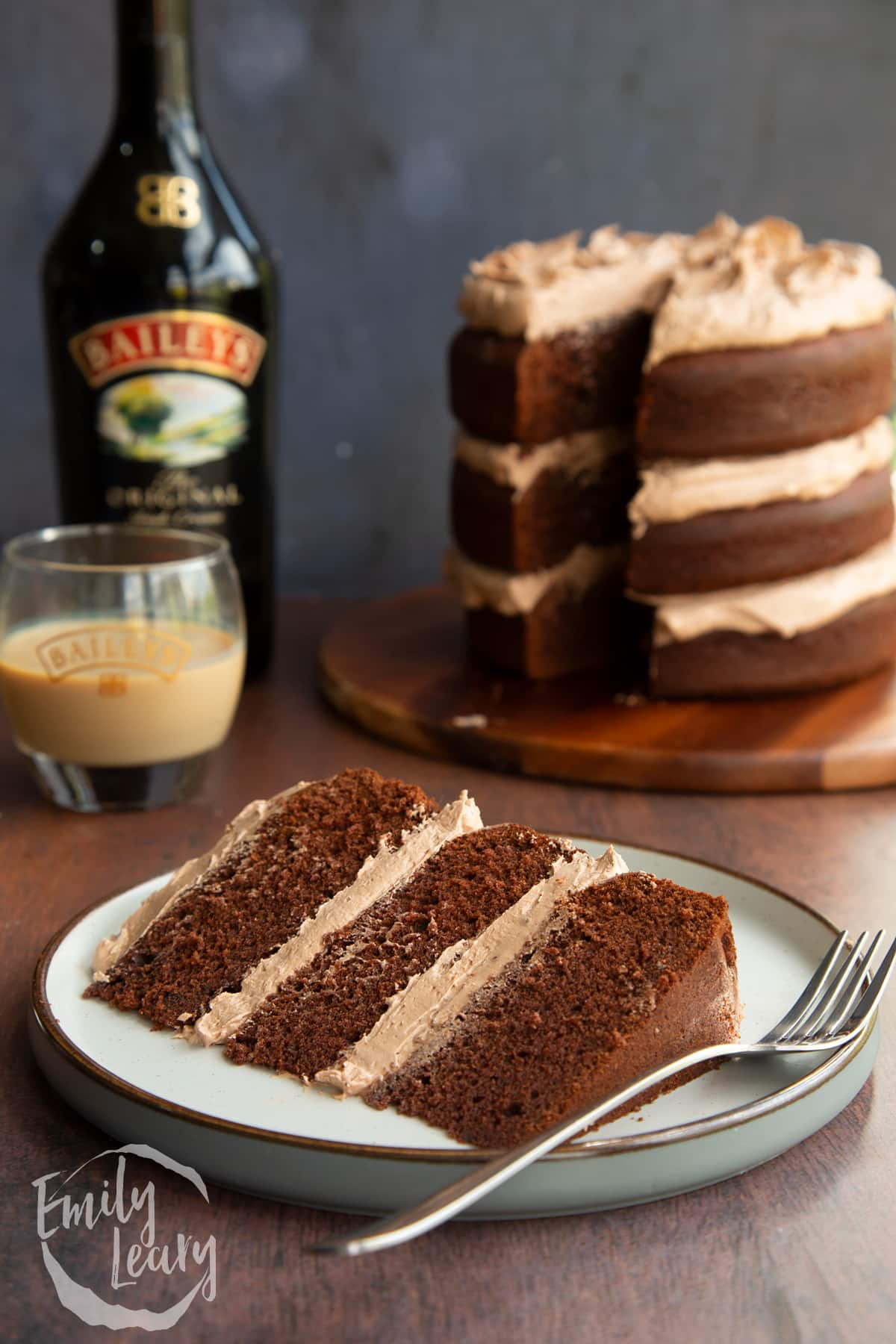 Slice of chocolate Baileys cake with Baileys buttercream frosting on a white plate with a fork.