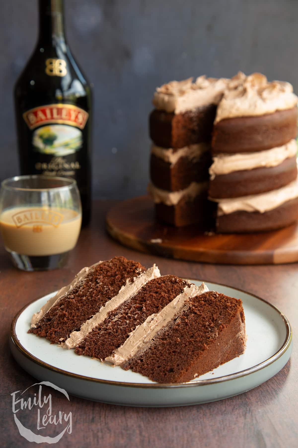 Slice of chocolate Baileys cake with Baileys buttercream frosting on a white plate.