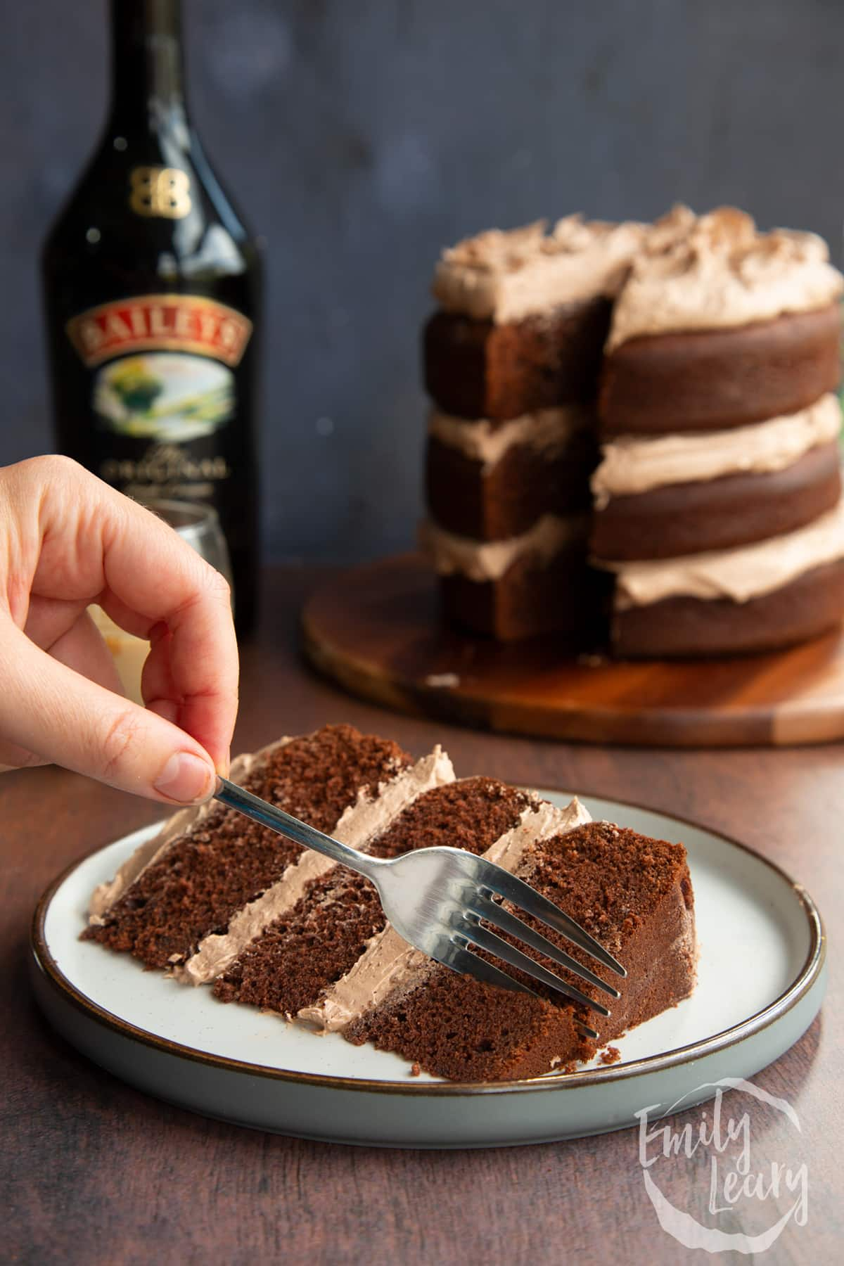 Slice of chocolate Baileys cake with Baileys buttercream frosting on a white plate with a fork delving into it