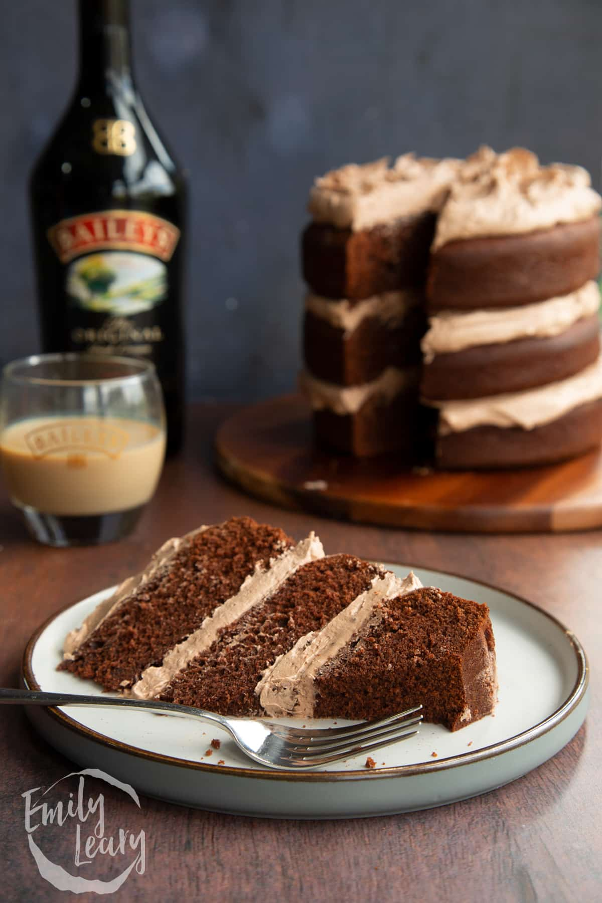 Slice of chocolate Baileys cake with Baileys buttercream frosting on a white plate with a piece cut away and a fork resting beside it.