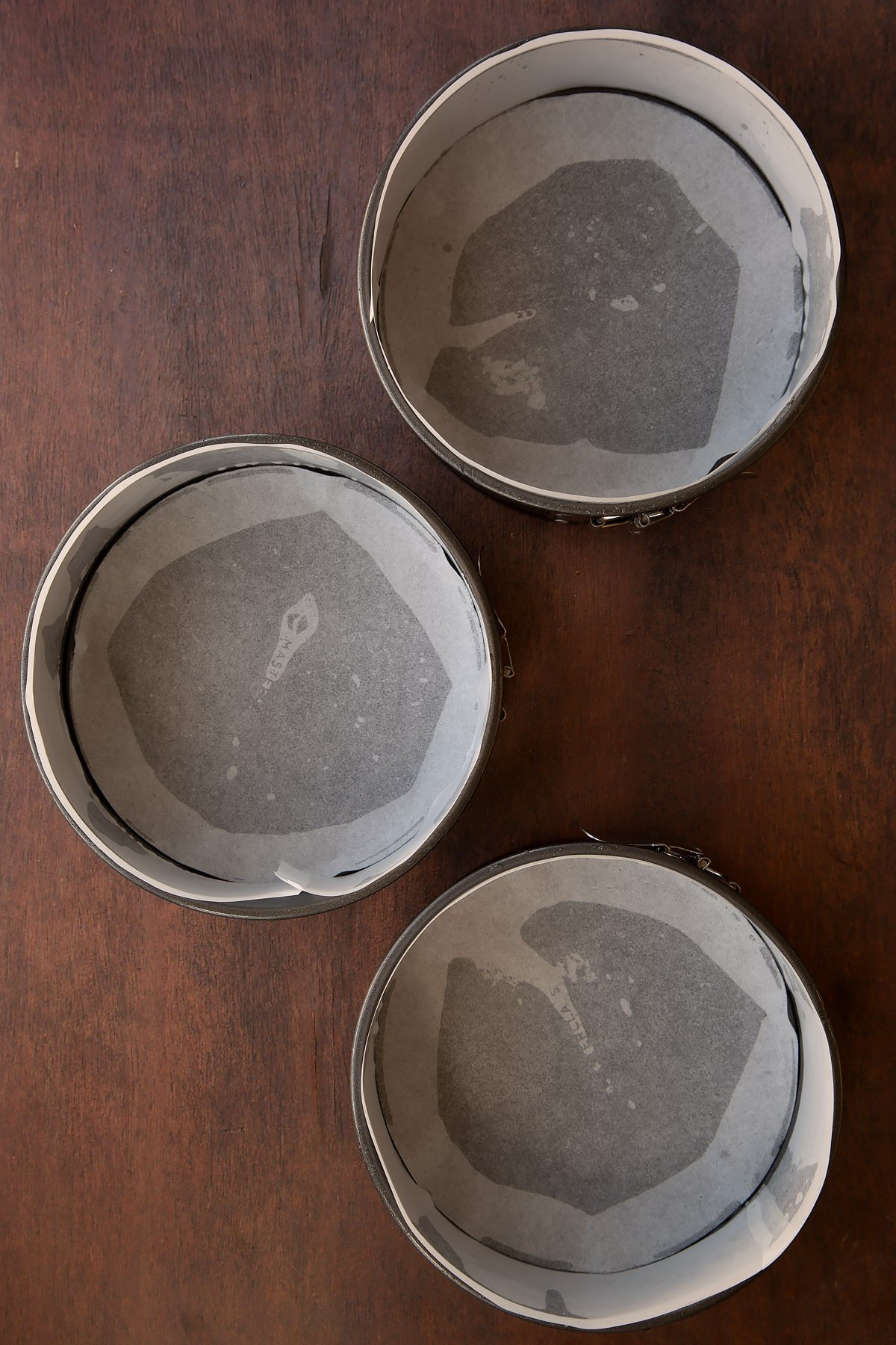 Three lined cake tins on a dark wooden surface.