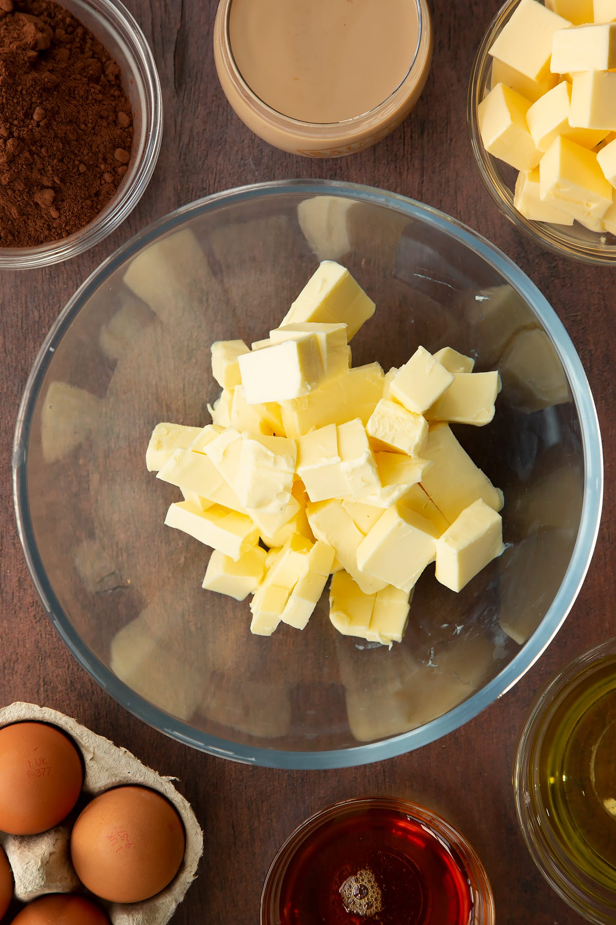 Cubed butter in a glass mixing bowl. Ingredients to make a Baileys cake surround the bowl.
