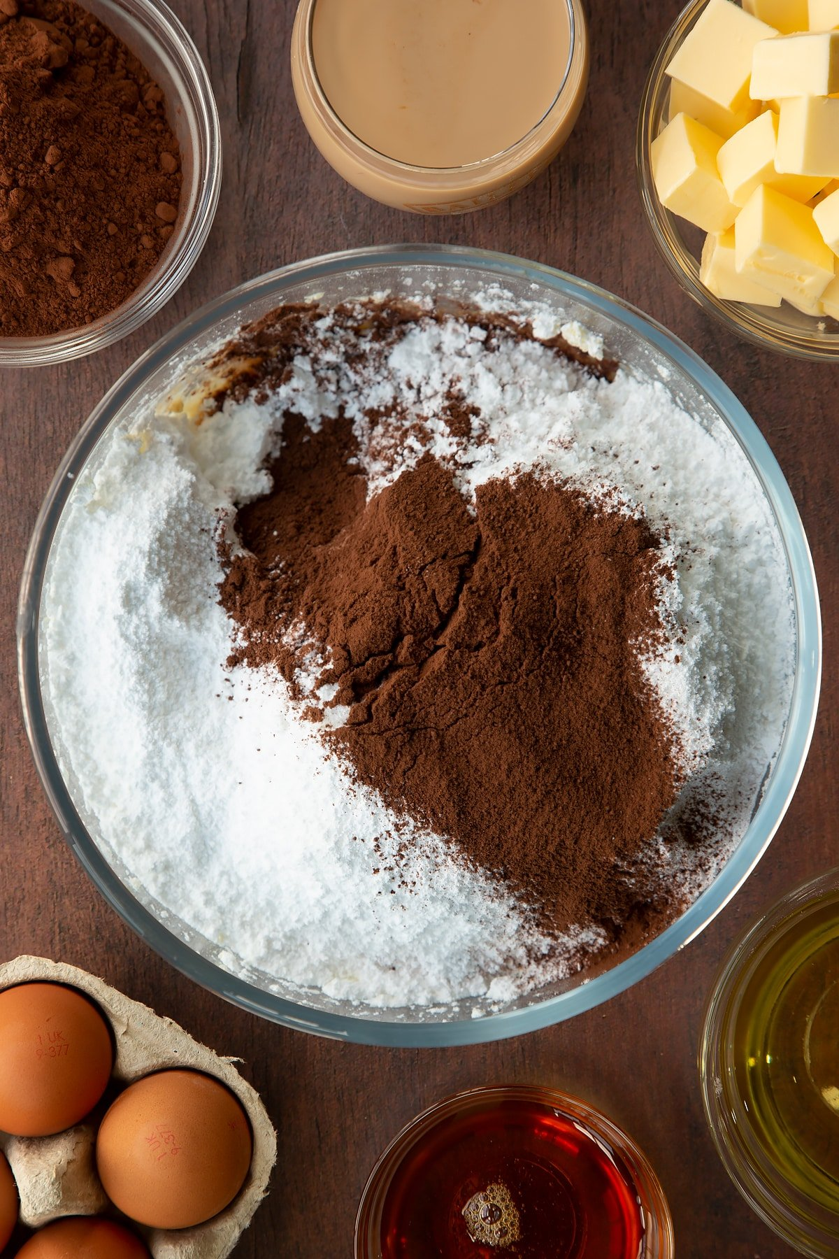 Whipped butter in a glass mixing bowl, topped with icing sugar, cocoa and Baileys. Ingredients to make a Baileys cake surround the bowl.