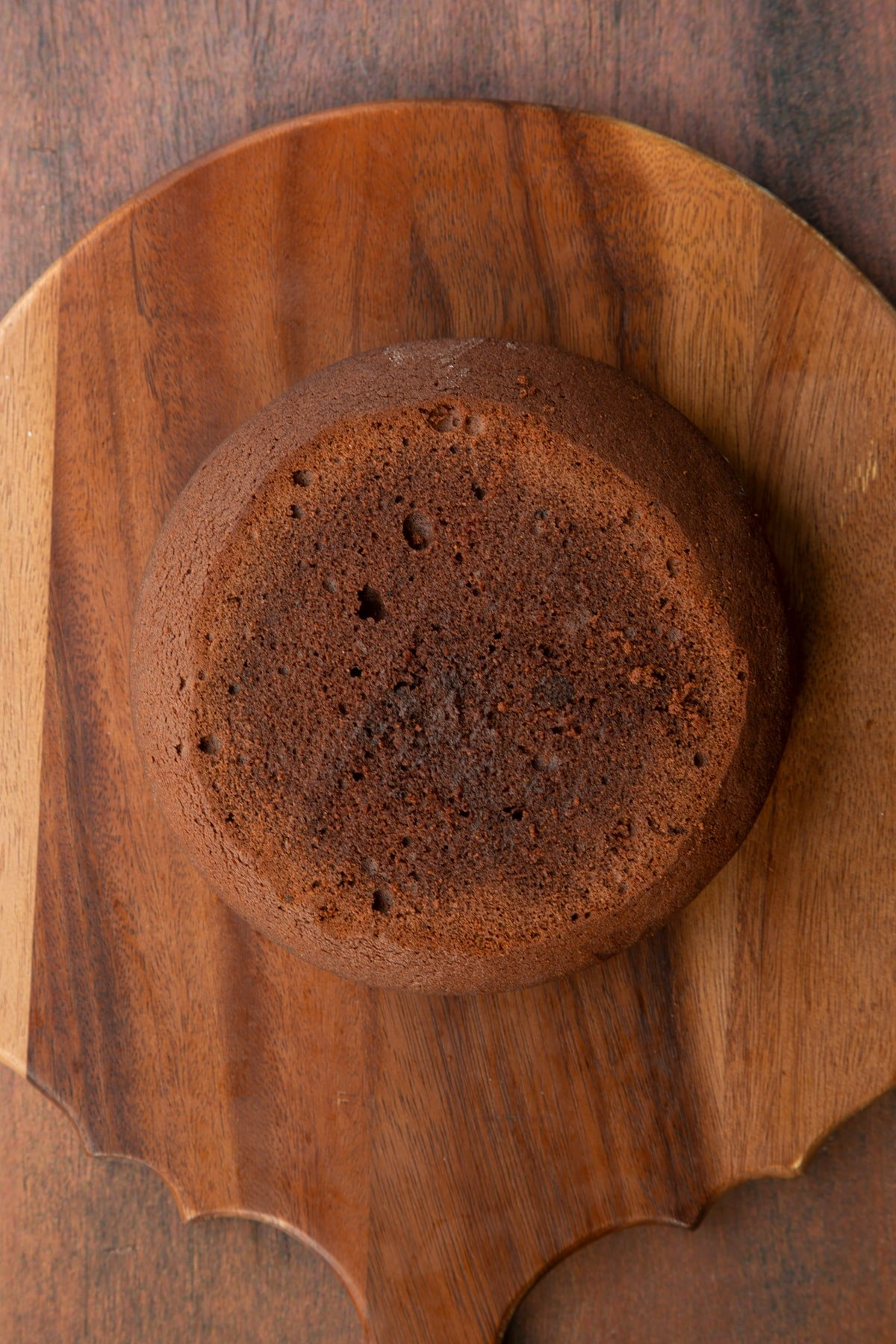 A layer of Baileys chocolate cake on a wooden board.