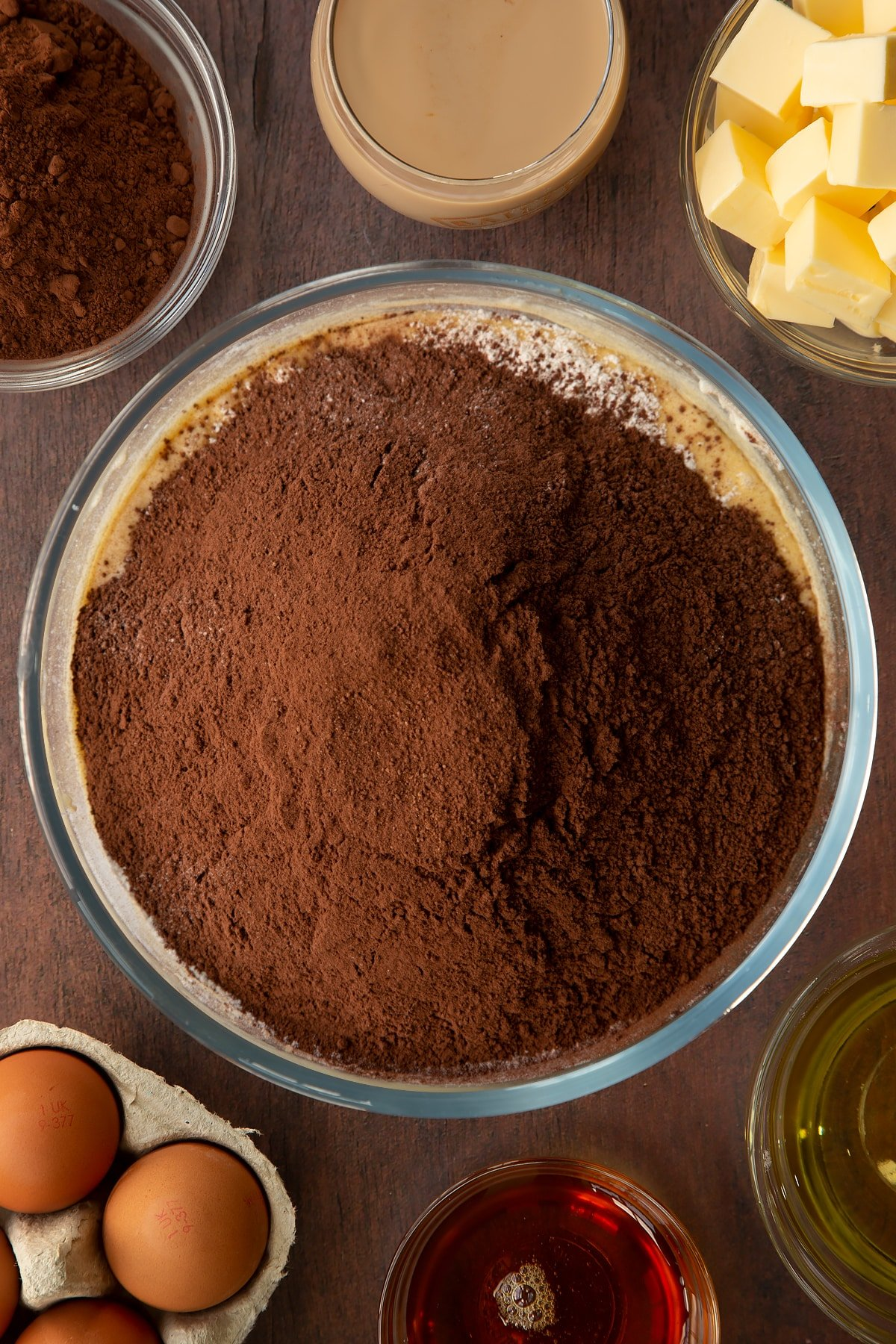 Butter, vegetable oil, caster sugar, golden syrup, egg and Baileys, whisked together in a glass mixing bowl with flour and cocoa on top. Ingredients to make a Baileys cake surround the bowl.