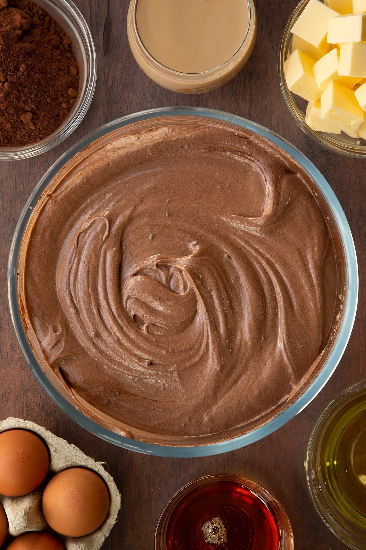 Chocolate Baileys cake batter in a glass mixing bowl. Ingredients to make a Baileys cake surround the bowl.