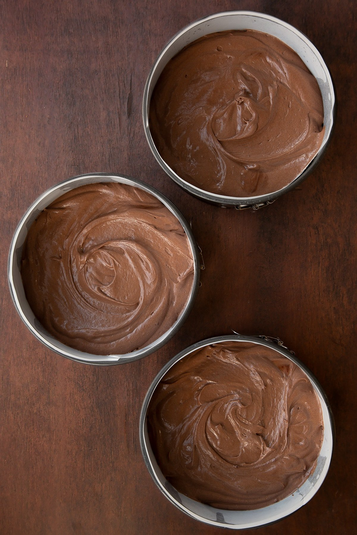 Chocolate Baileys cake batter in three lined cake tins.