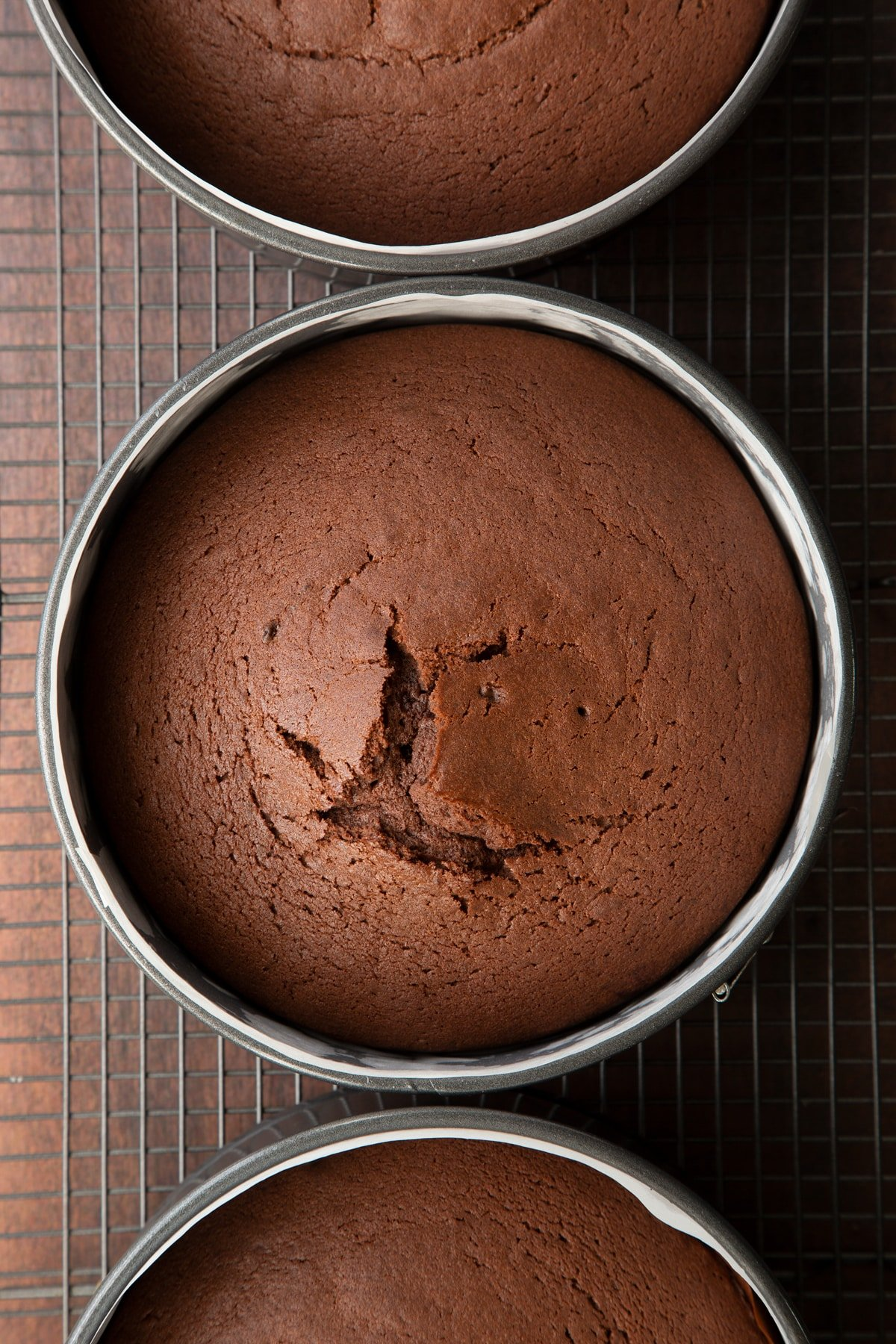 Freshly baked chocolate Baileys cake in three lined tins on a wire cooling rack.