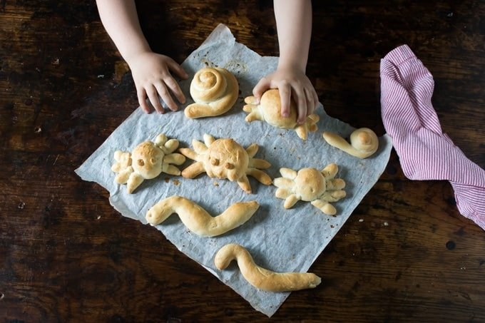 Bread in the shape of spiders and snakes on baking paper. A child's hands reach for the bread.