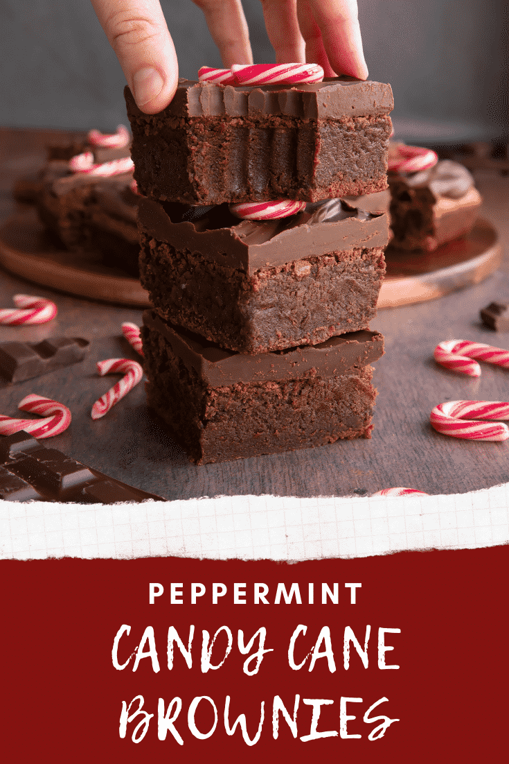 A stack of candy cane brownies. A hand reaches for one with a bite out of it. Caption reads: Peppermint candy cane brownies.