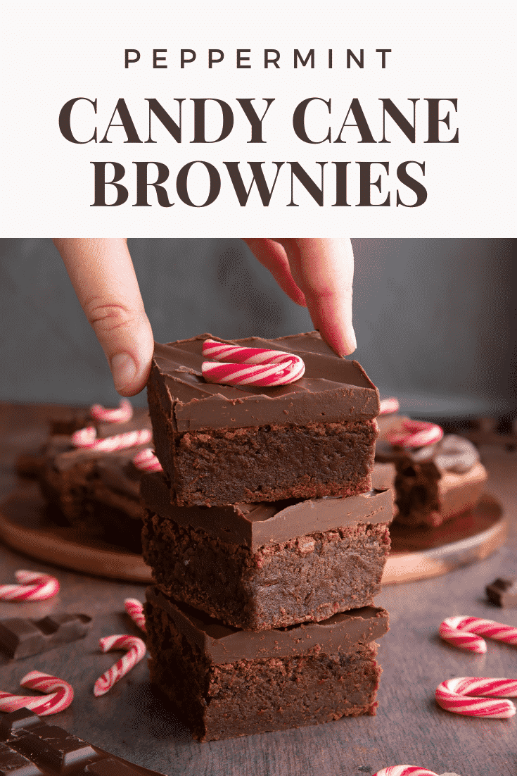 A stack of candy cane brownies. A hand reaches for one. Caption reads: Peppermint candy cane brownies.