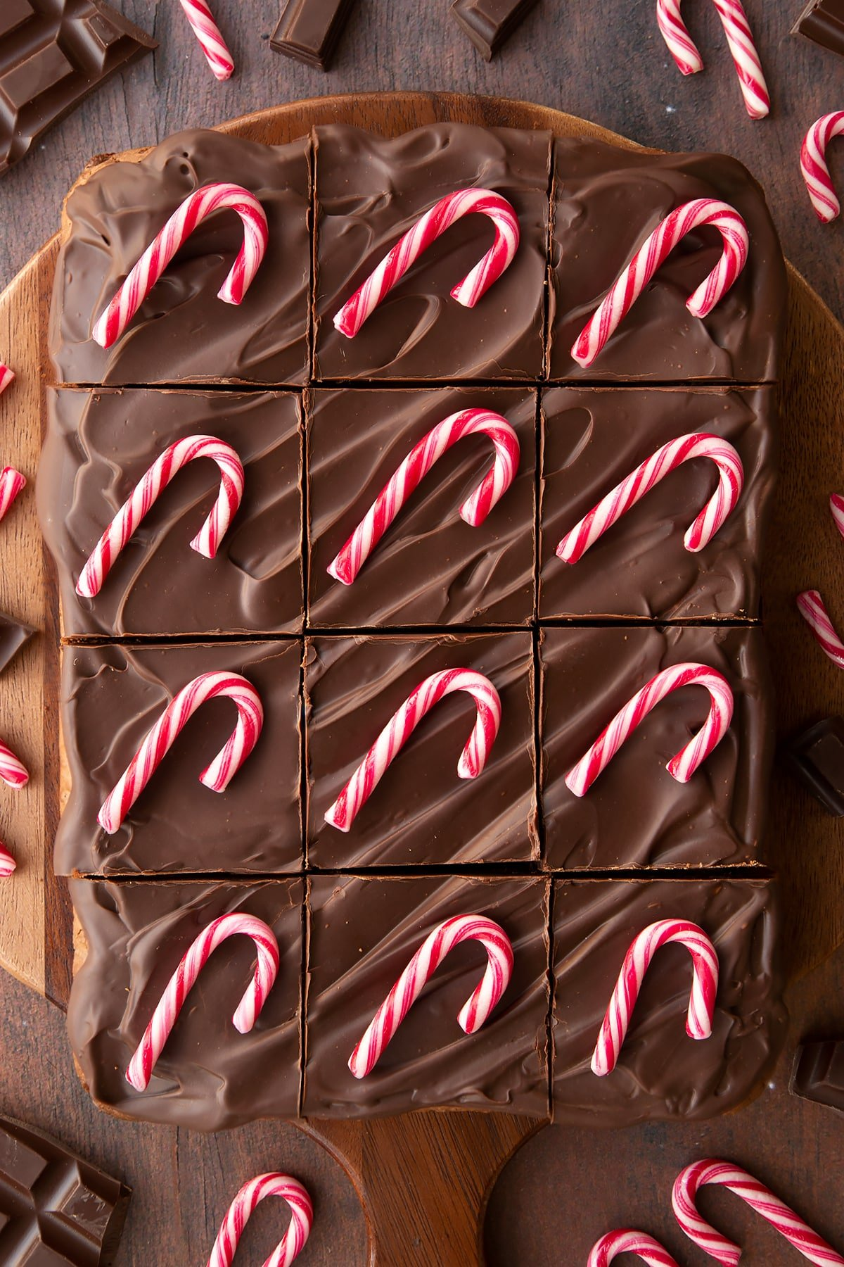 Candy cane brownies on a board, cut into 12 pieces. Each piece has been topped with a candy cane.