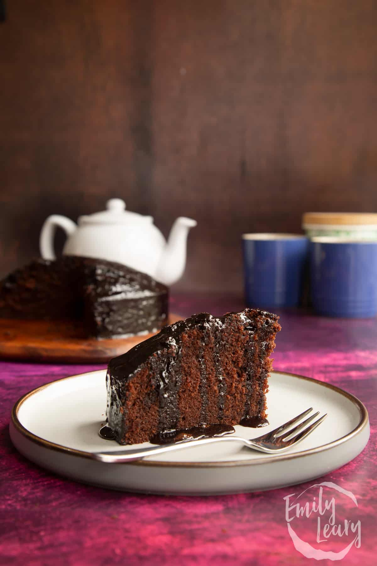 A slice of chocolate drizzle cake on a plate with a fork.