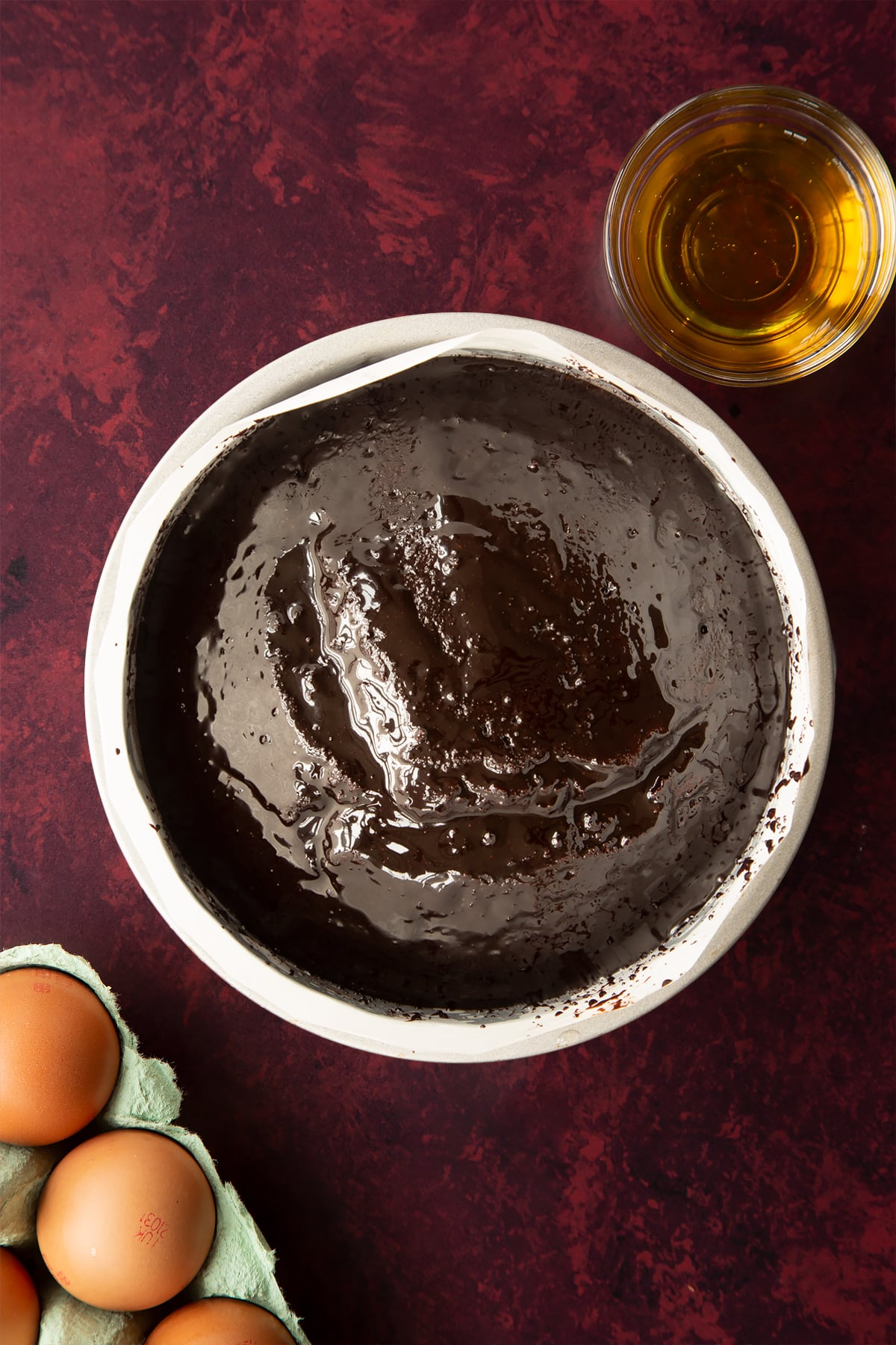 Chocolate drizzle cake, drizzled with syrup in a lined tin.