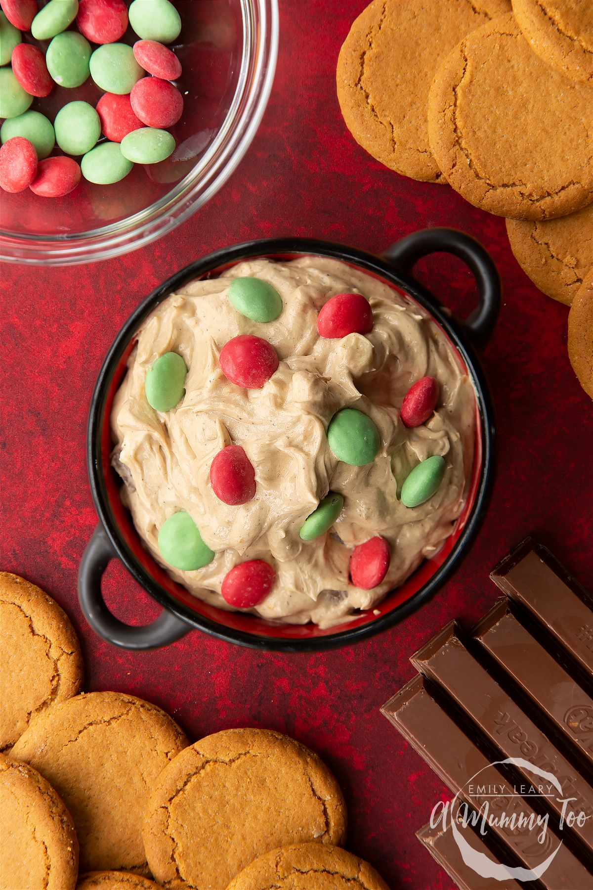 Christmas cookie dip in a black pot, surrounded by ingredients. Shown from above.