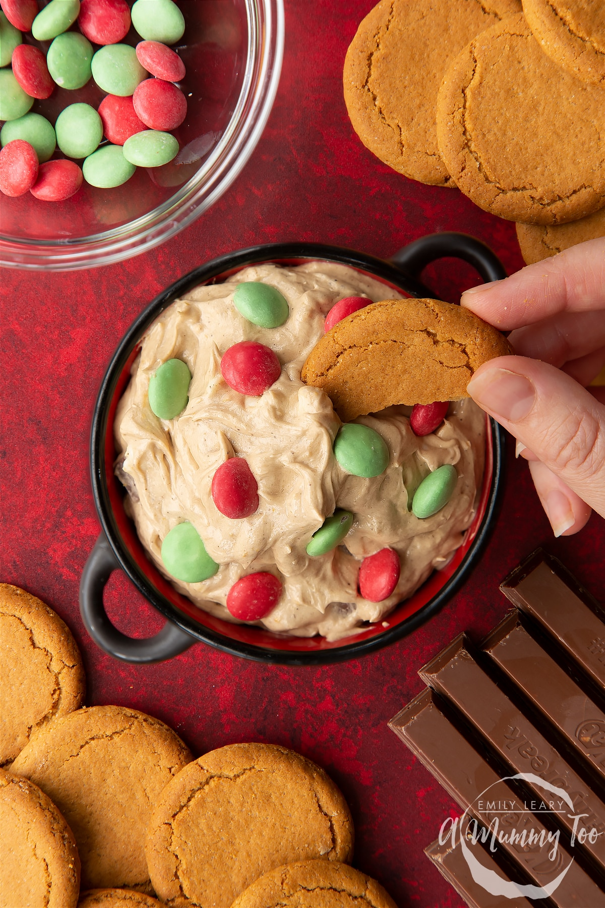 Christmas cookie dip in a black pot. A hand dips a piece of gingernut cookie into the dip. Shown from above.