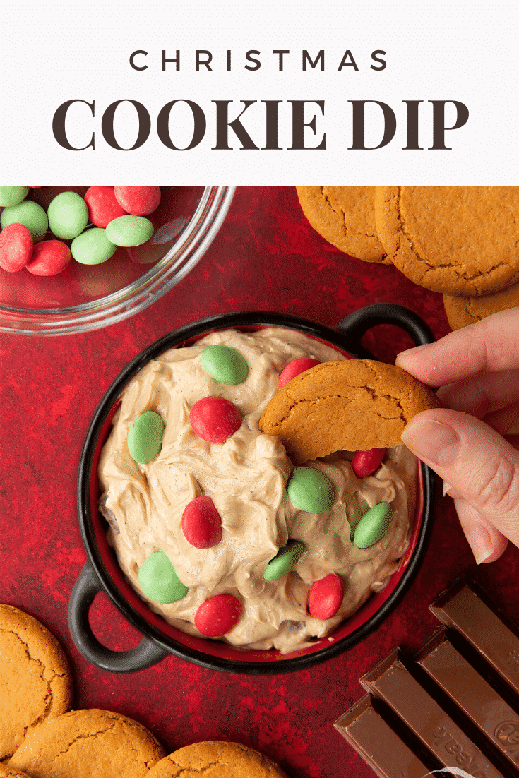 Christmas cookie dip in a black pot. A hand dips a piece of gingernut cookie into the dip. Caption reads: Christmas cookie dip.