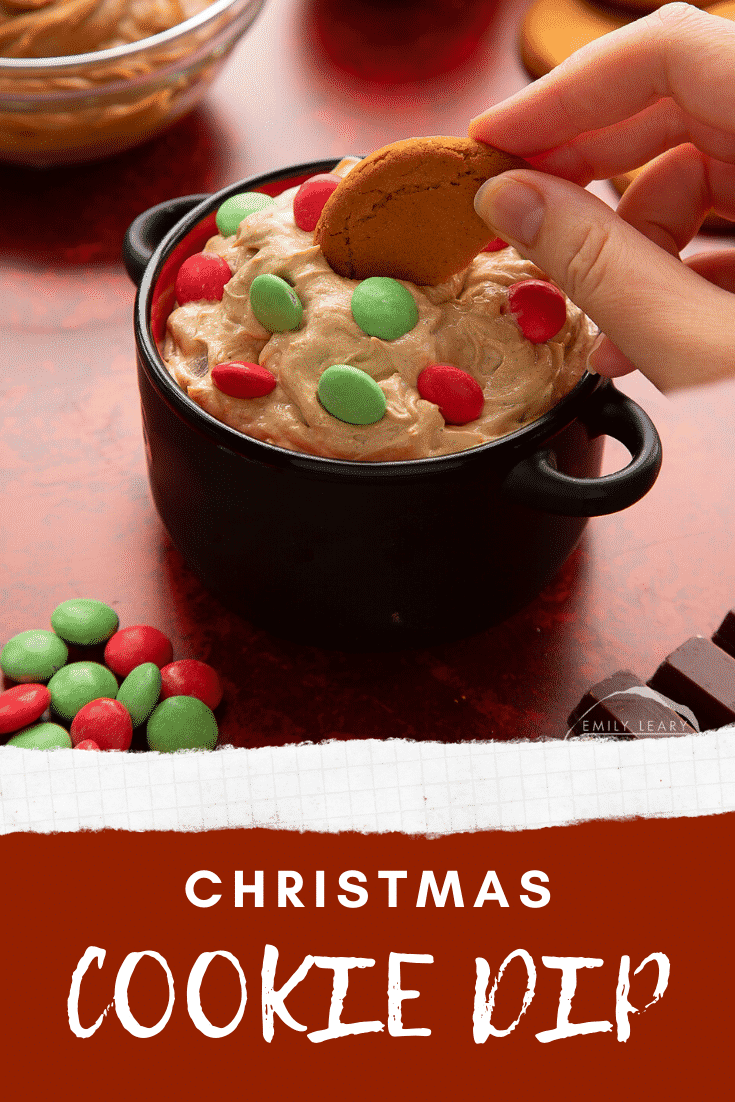 Christmas cookie dip in a black pot. A hand dips a gingernut cookie into the dip. Caption reads: Christmas cookie dip.