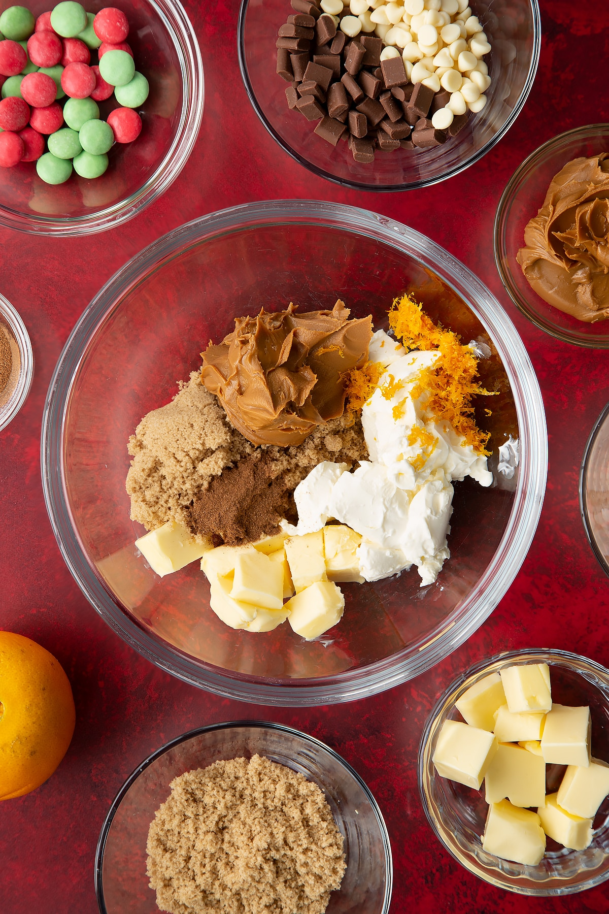 Butter, cream cheese, Biscoff spread, sugar, orange zest and cinnamon in a mixing bowl.Ingredients to make Christmas cookie dip surround the bowl.