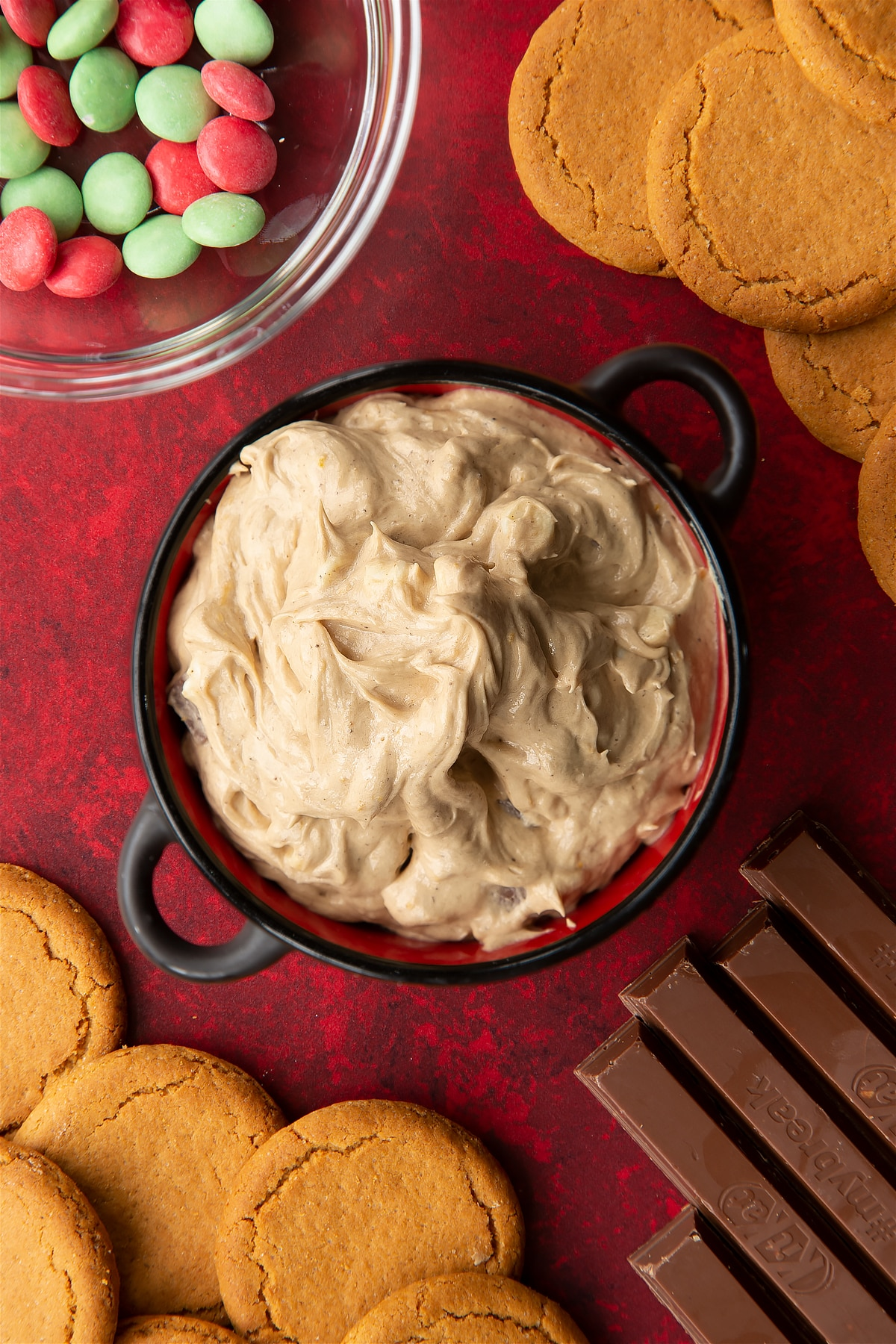Christmas cookie dip in a black pot.Ingredients to make Christmas cookie dip surround the bowl.