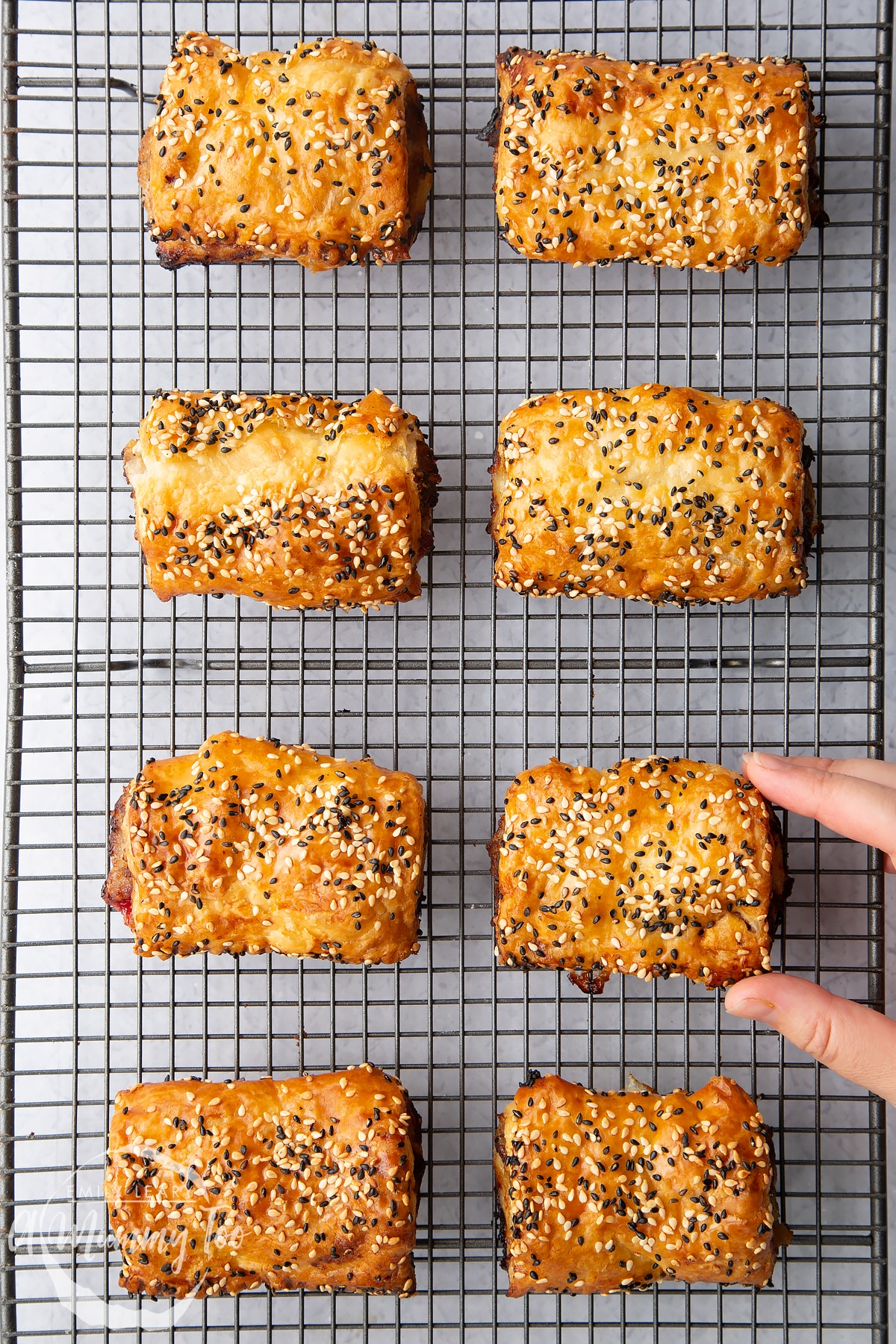 Festive sausage rolls on a wire cooling rack. A hand reaches for one.
